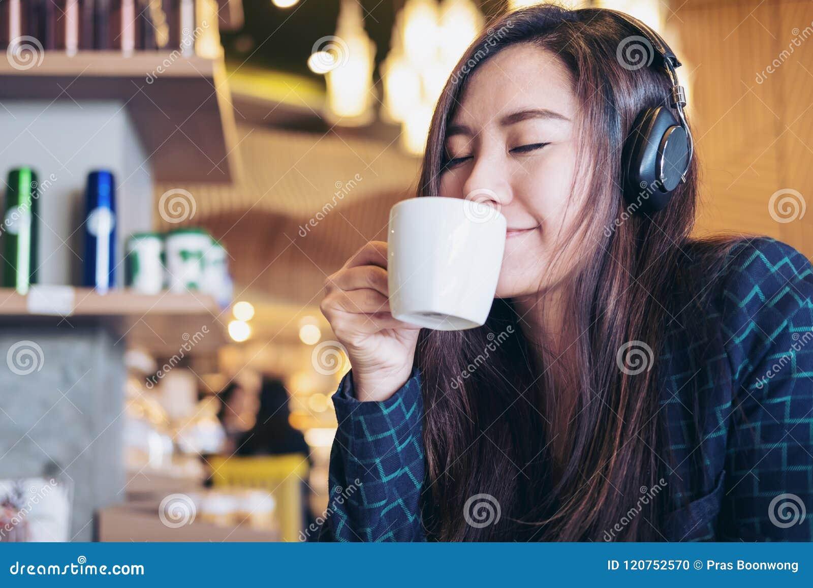 Det asiatiska kvinnaslutet henne ögon och att lyssna till musik med headphonen, medan dricka kaffe med mening lyckligt, och koppl