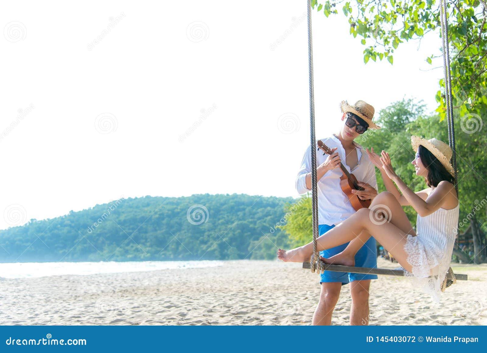 Det asiatiska romantiska paret sitter p? havsstranden p? repgunga kopplar av och lycka f?r ferie Br?llopsresa kopplar av tillsamm
