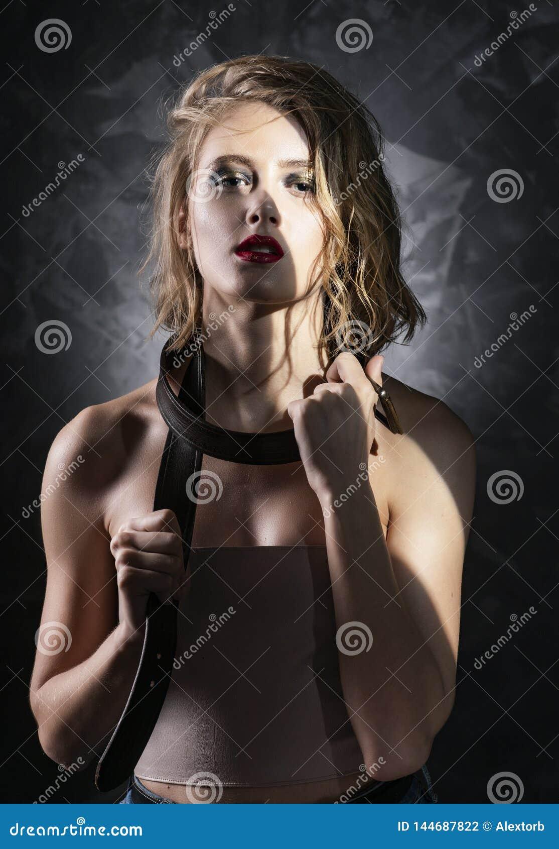 Det begreppsm?ssiga fotoet av en ung flicka med ov?rdat v?tt h?r, nakna skuldror, aggressivt smink, och m?n piskar b?ltet omkring