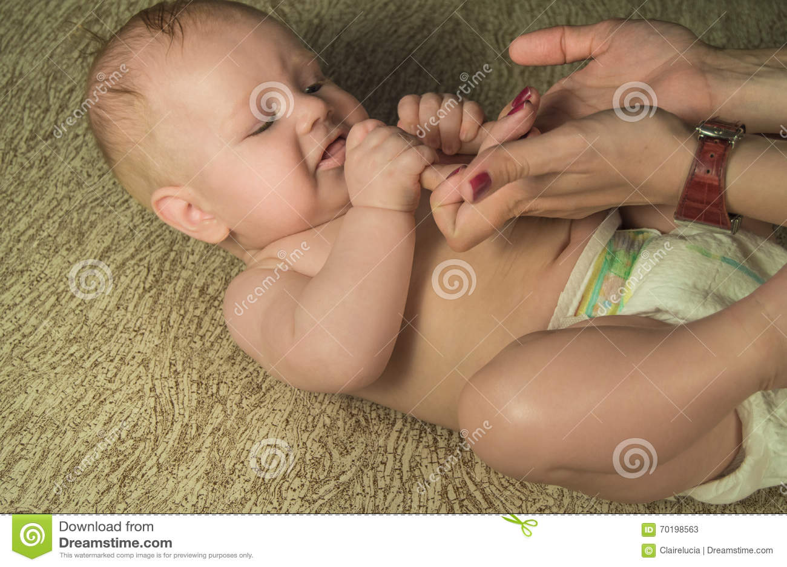 Det begynnande barnet av 4 månader håller hans moders fingrar
