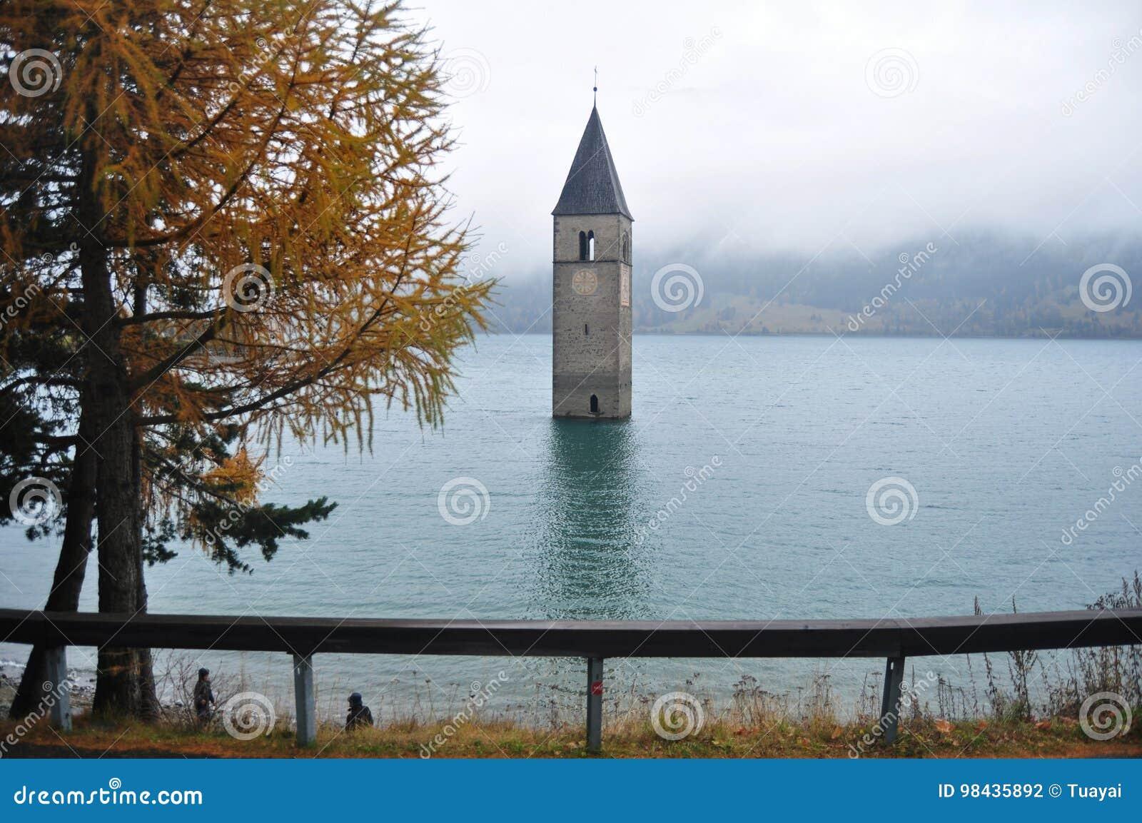 Det doppade tornet av reschenseekyrkan djupt i Resias sjön av Bolzano eller bozen, Italien