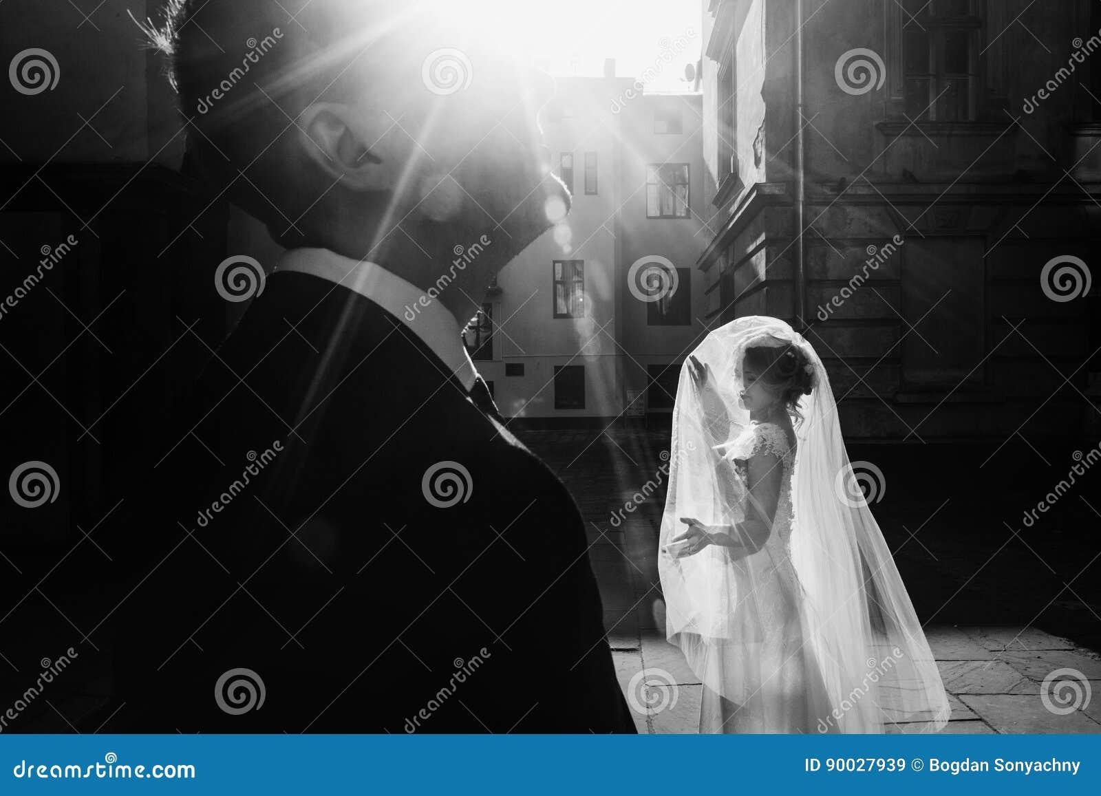Det eleganta brudinnehavet skyler och posera med brudgummen i solljusund