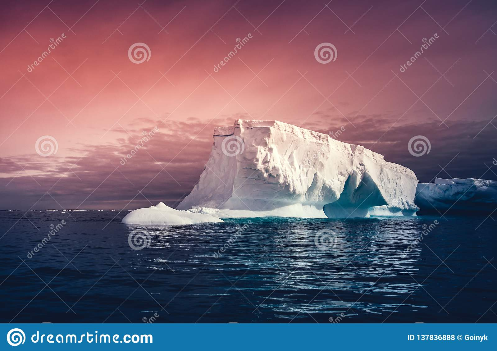 Det enorma isberget på den färgrika himmelbakgrunden