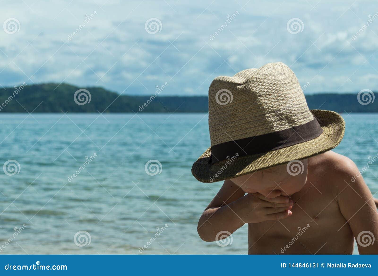 Det europeiska lilla barnet nyser, på bakgrunden av havet Barnet var sjukt på ferie
