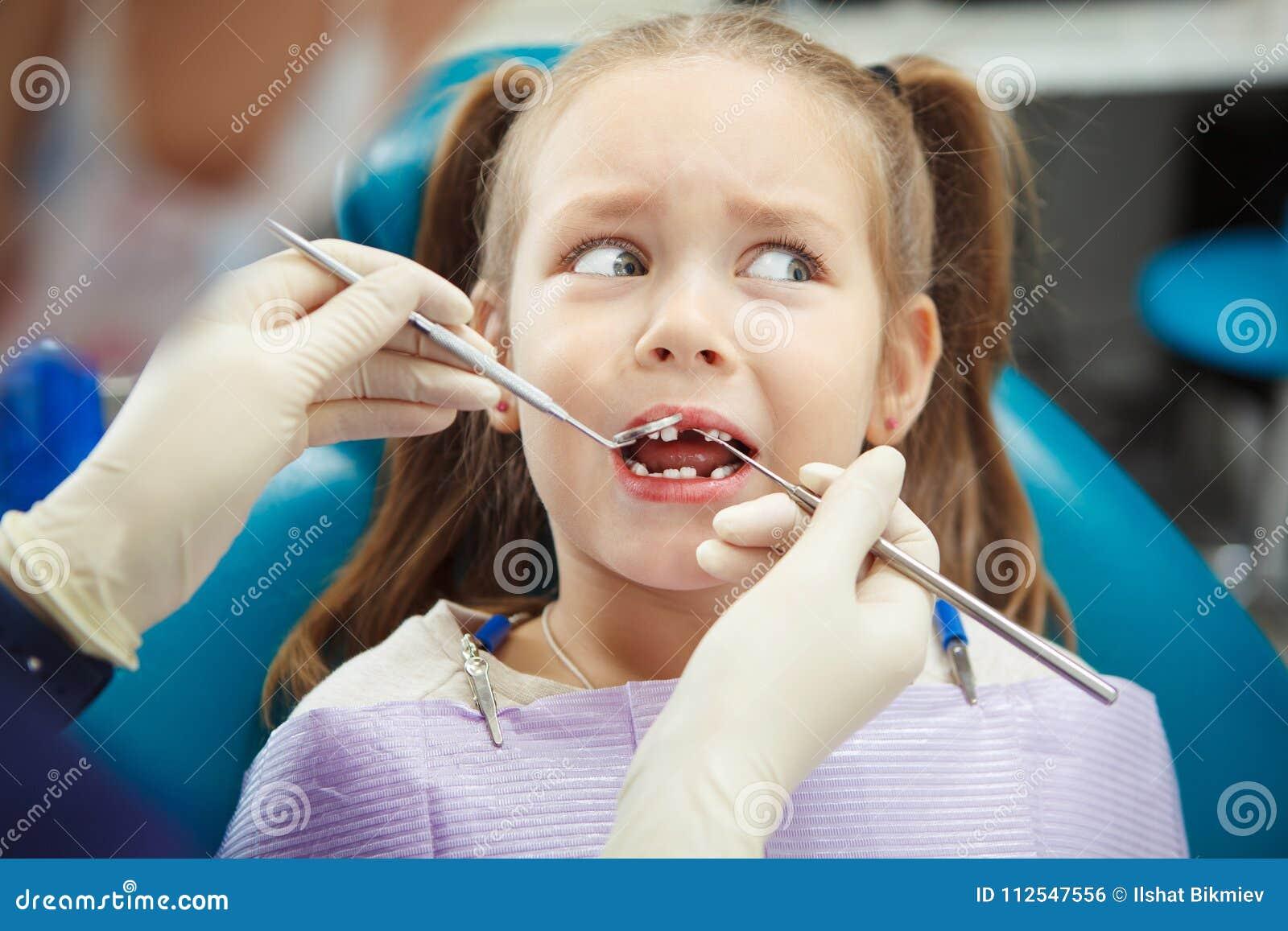 Det förskräckta barnet sitter på tandläkarestol med den öppna munnen