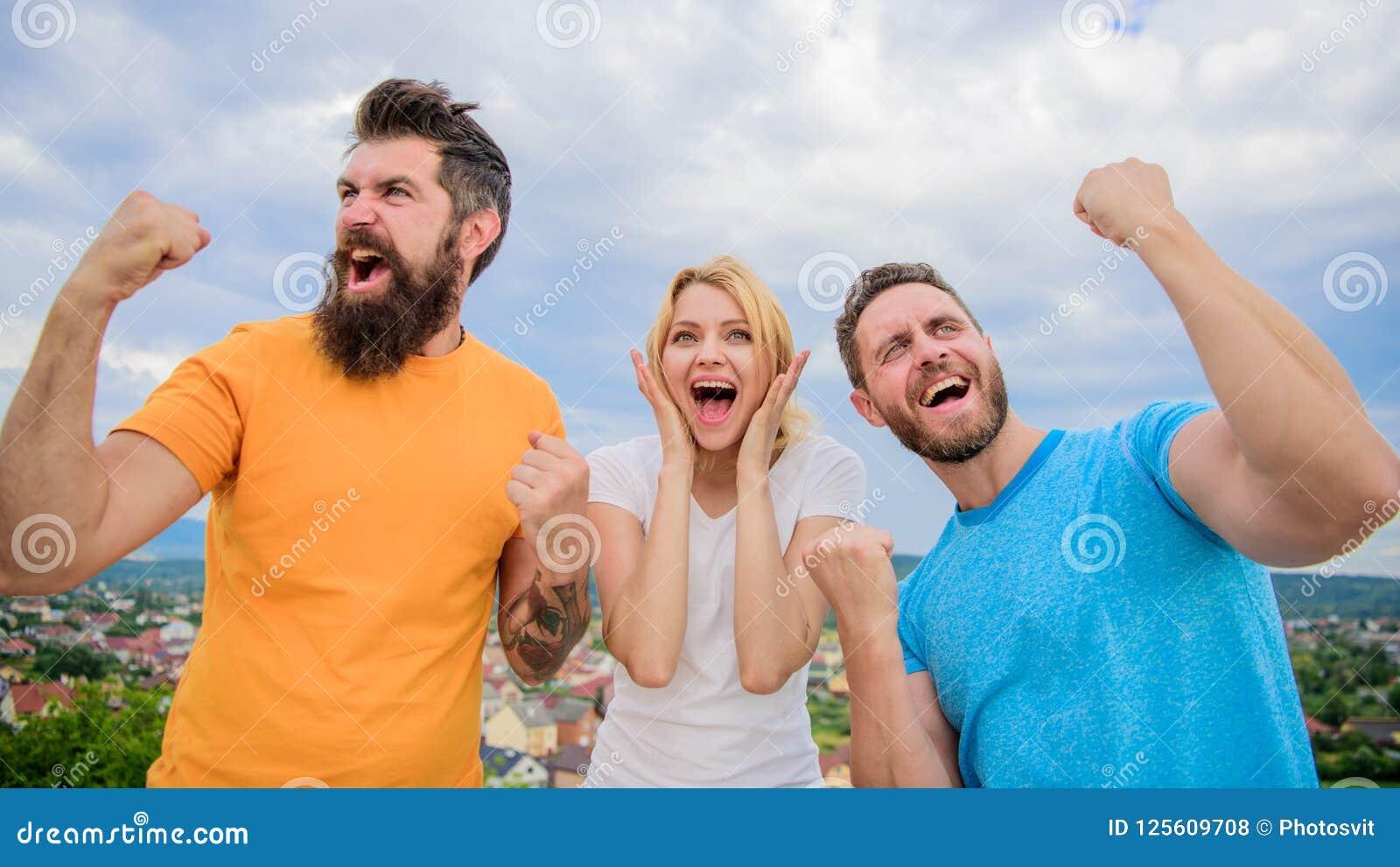 Det favorit- laget segrade konkurrens Kvinnan och män ser lyckade firar segerhimmelbakgrund Lycklig Threesomeställning