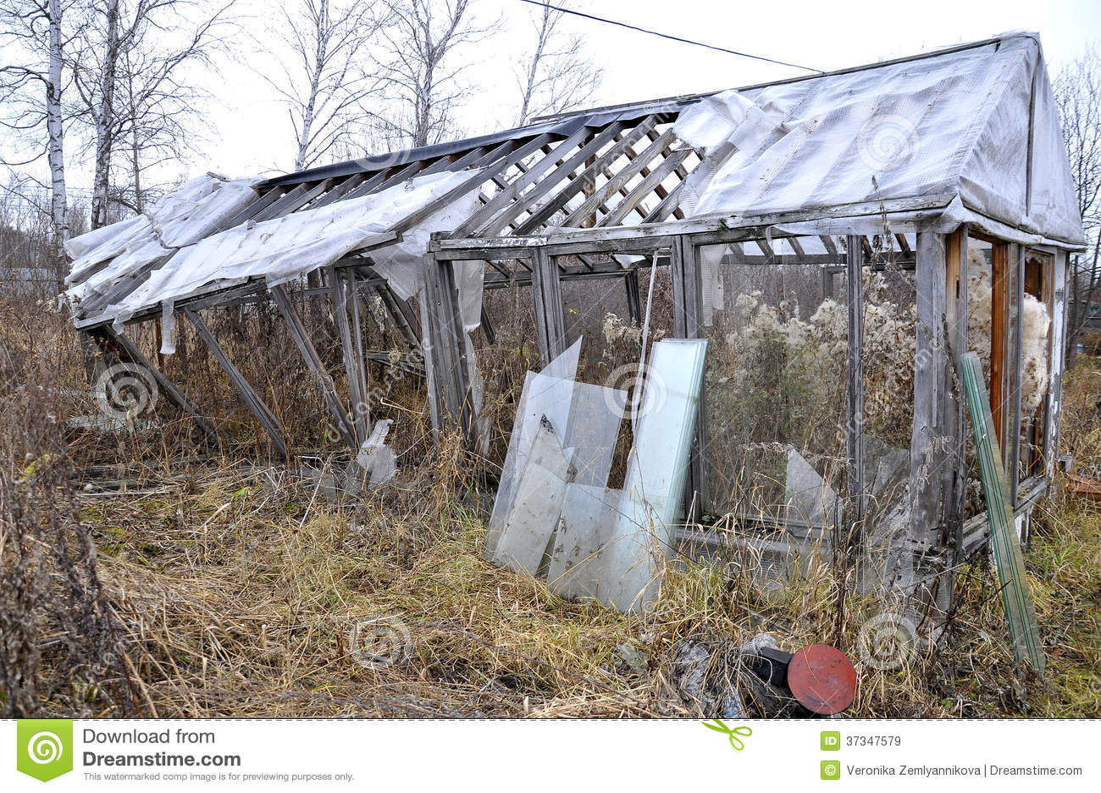 Det gamla brutna träväxthuset i en kökträdgård.