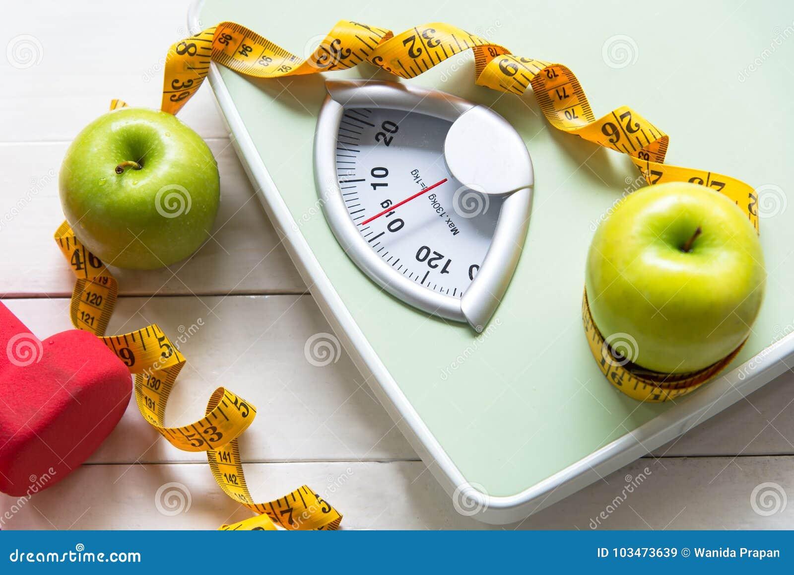 Det gröna äpplet med viktskalan och mätabandet för det sunt bantar bantning