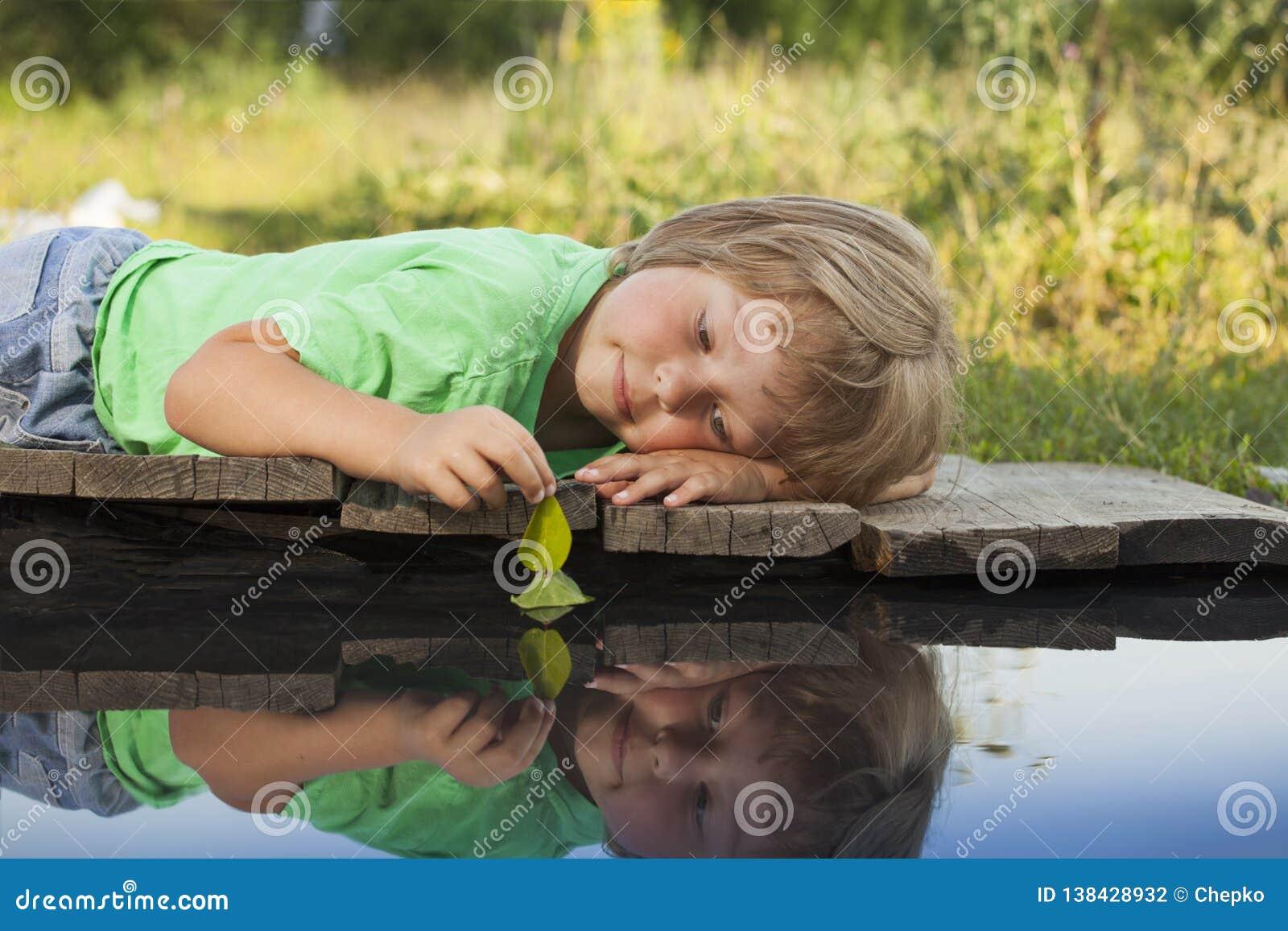 Det gröna blad-skeppet i barnhand i vatten, pojke parkerar in lek med fartyget i floden