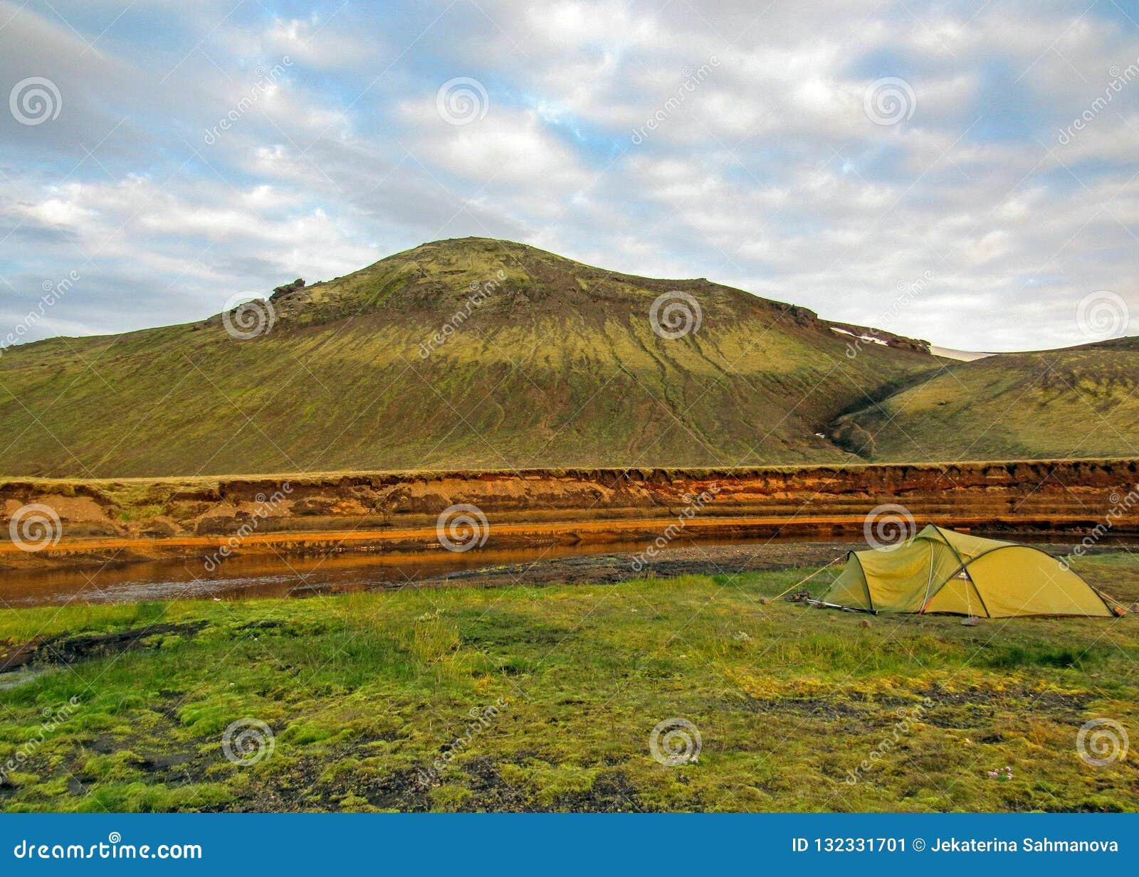 Det gröna tältet kastade bredvid floden med det gröna berget i bakgrunden, den Alftavatn campingplatsen, Laugavegur, Island