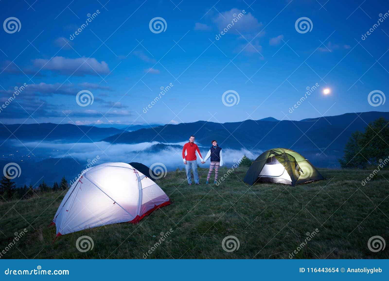 Det gulliga paret står nära campa rymmande händer mot bakgrunden av morgonberglandskap