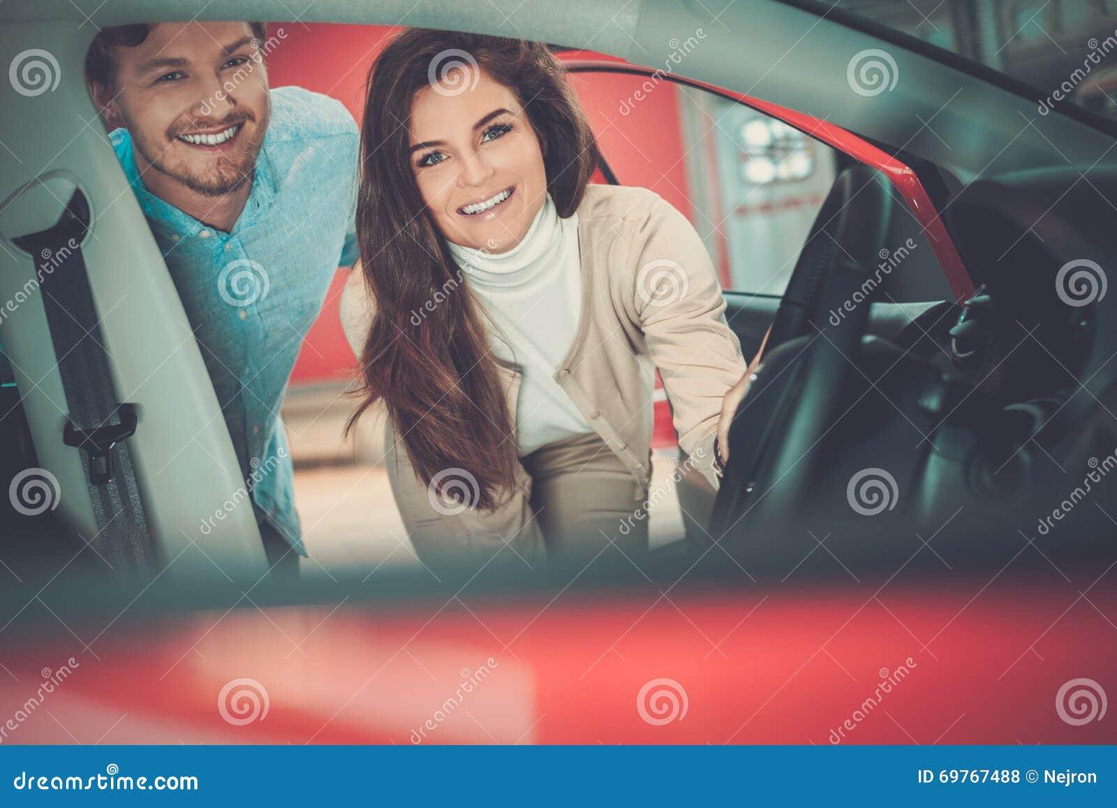 Det härliga barnet kopplar ihop att se en ny bil på återförsäljarevisningslokalen