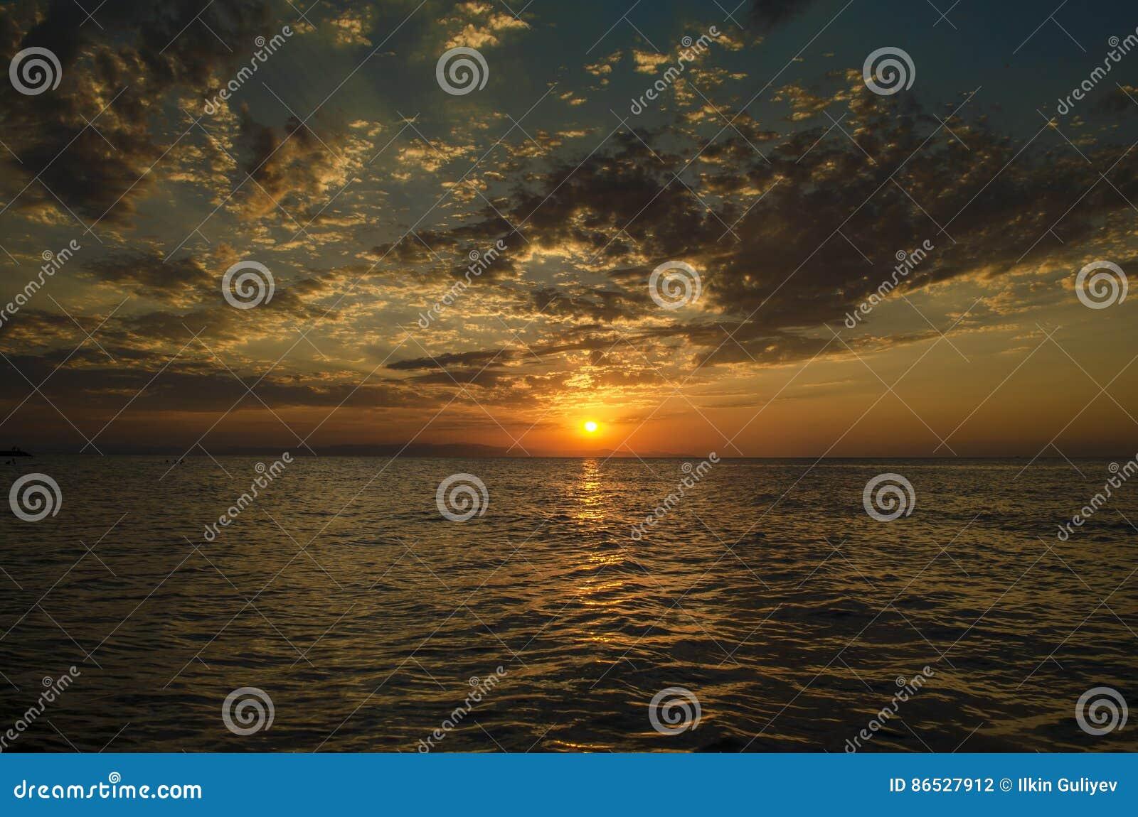 Det härliga flammande solnedgånglandskapet på Kaspiska hav- och apelsinhimmel ovanför det med guld- reflexion för enorm sol på st