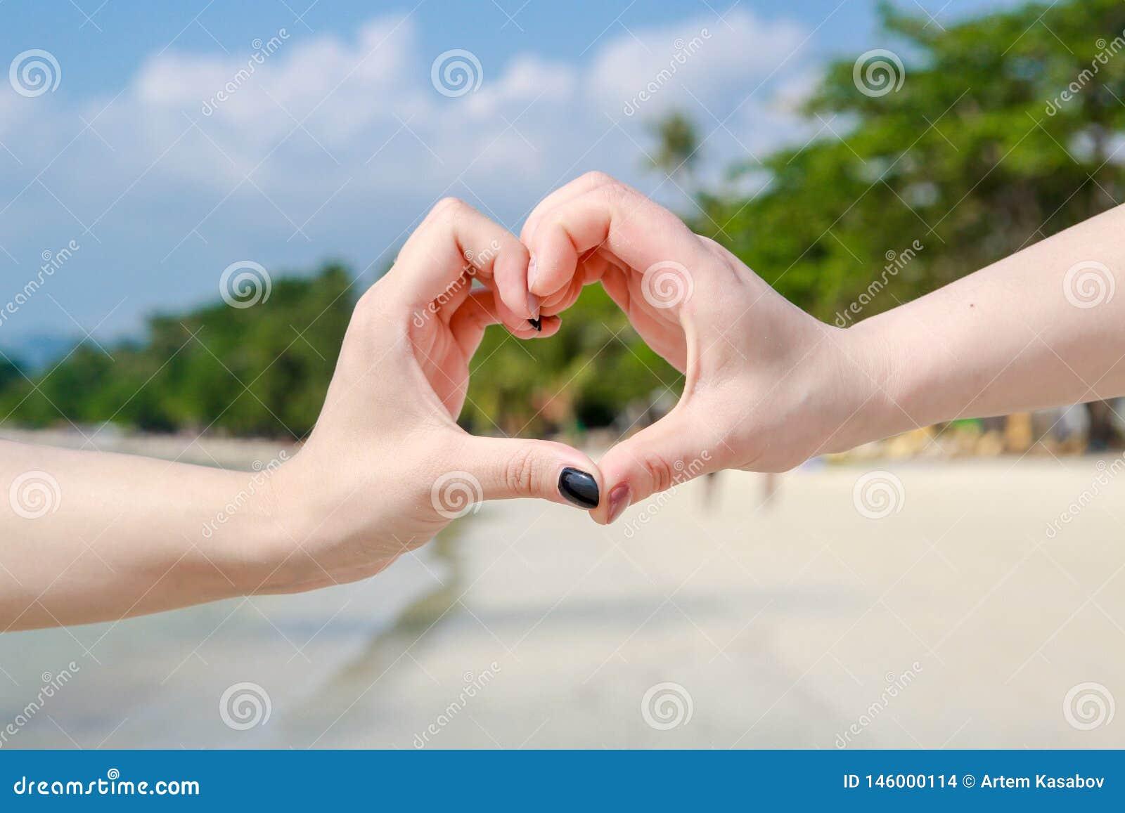 Det härliga unga paret gör hjärta med fingrarna