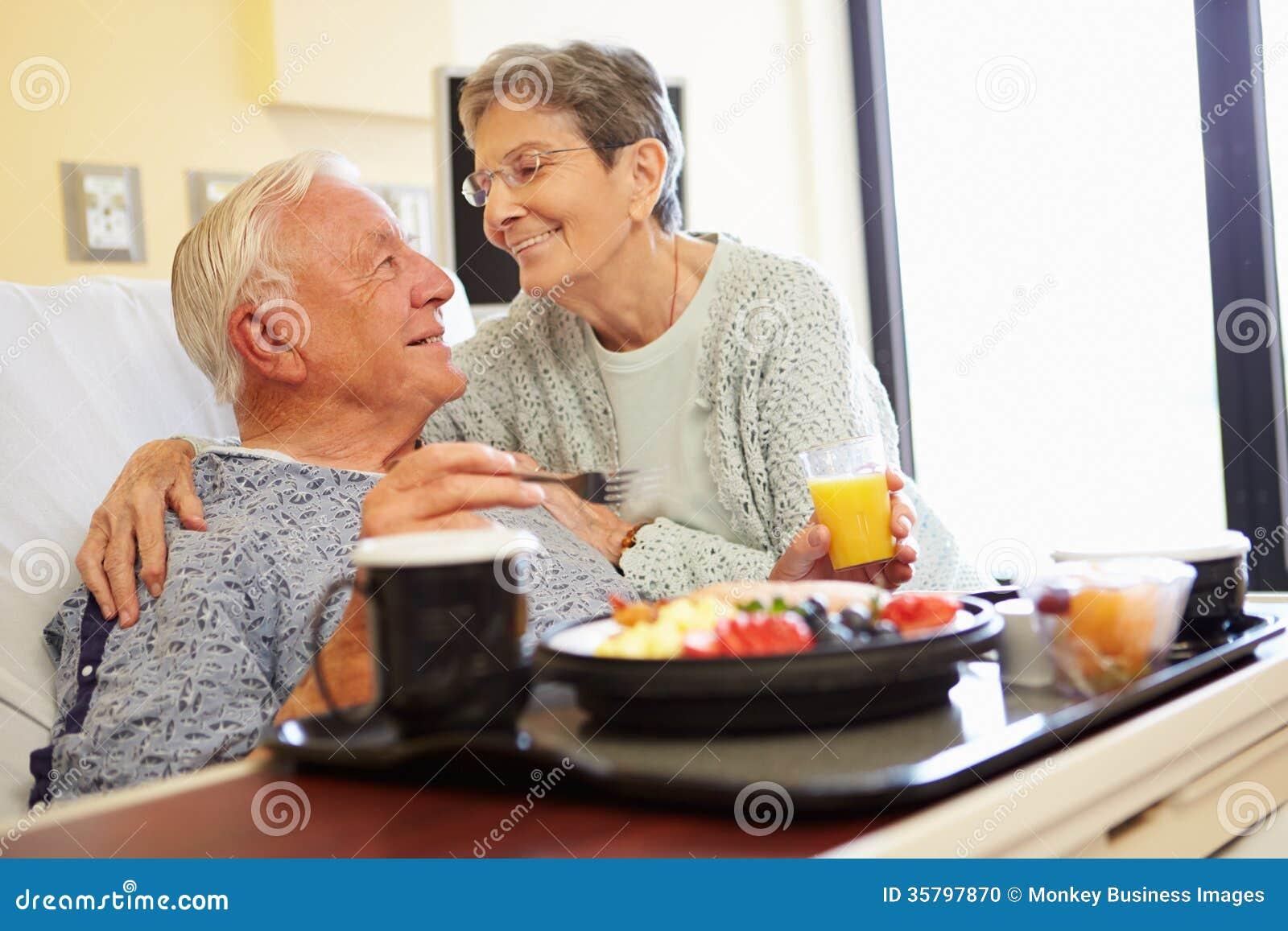 Det höga paret i sjukhusrum som den manliga patienten har lunch