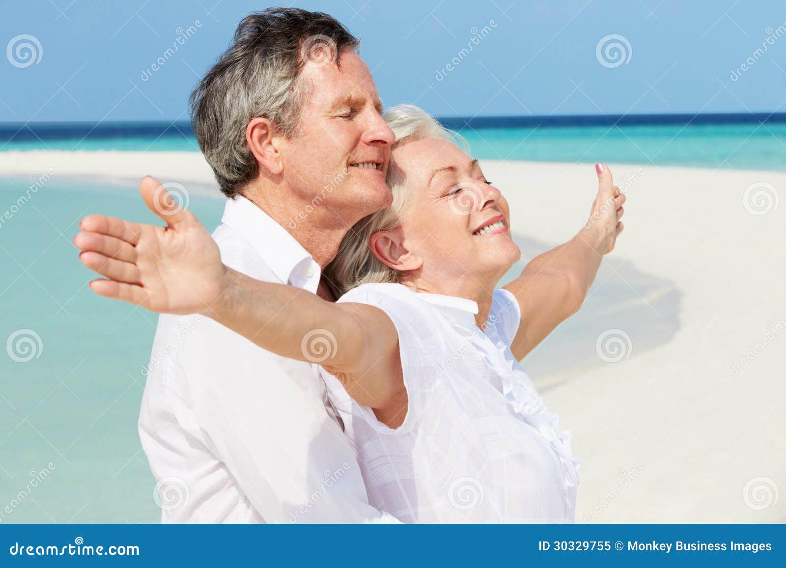 Det höga paret Withs beväpnar utsträckt på den härliga stranden
