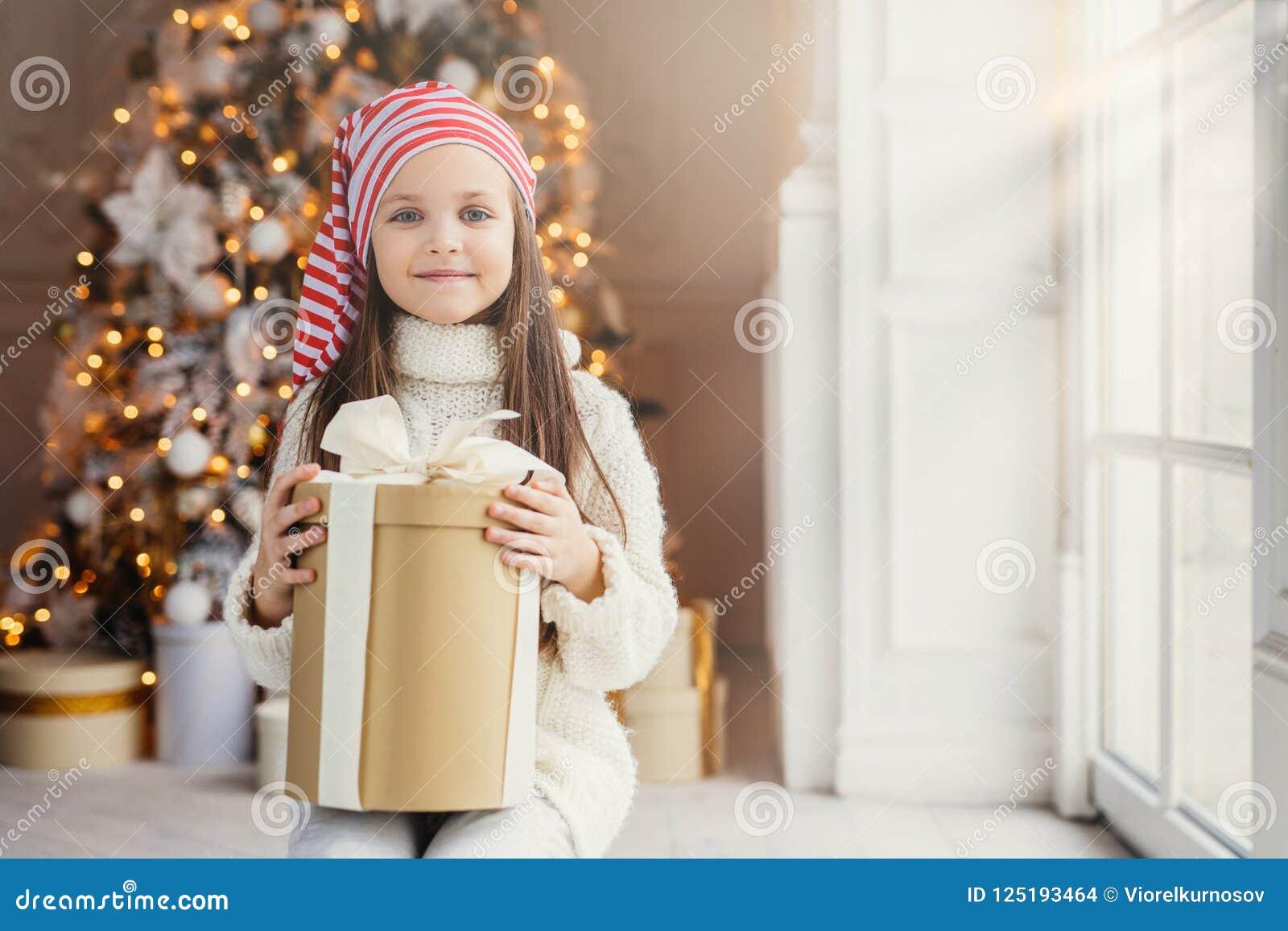 Det inomhus skottet av den angenäma seende lilla ungen med blått charma synar, bär den santa hatten, håll framlägger i slågen in
