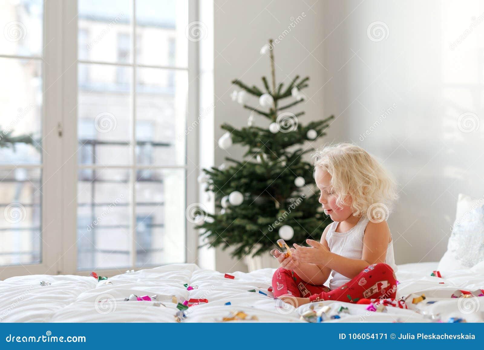 Det inomhus skottet av den blonda lockiga lilla ungen sitter korsade ben på bekväm säng, spelar med färgglad legitimationshandlin