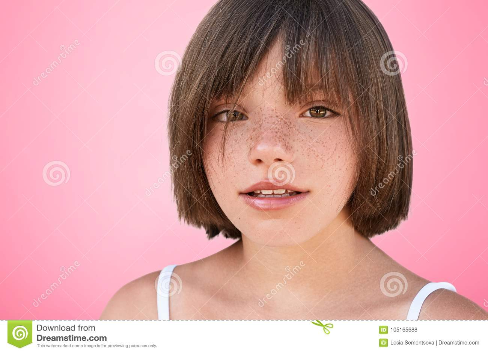 Det inomhus skottet av det säkra fräkniga härliga lilla kvinnliga barnet med den guppade frisyren ser kameran som är glad att fot