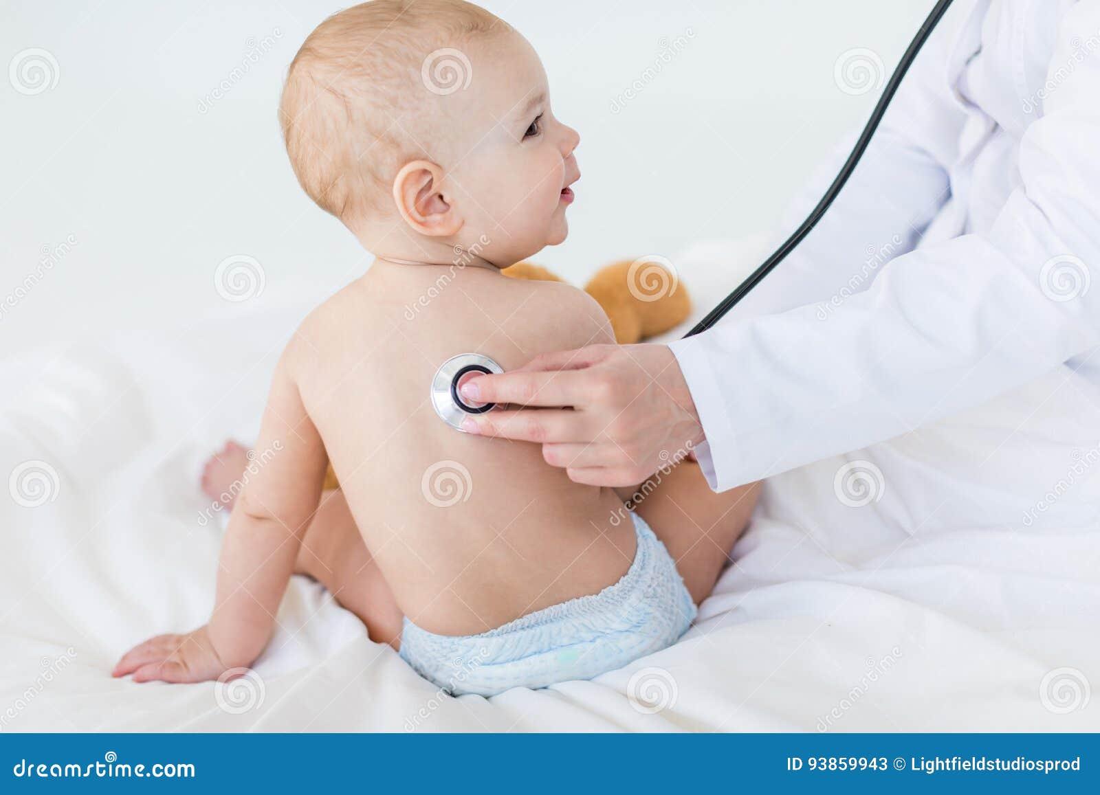 Det kantjusterade skottet av den medicinska arbetaren som undersöker, behandla som ett barn pojken med stetoskopet
