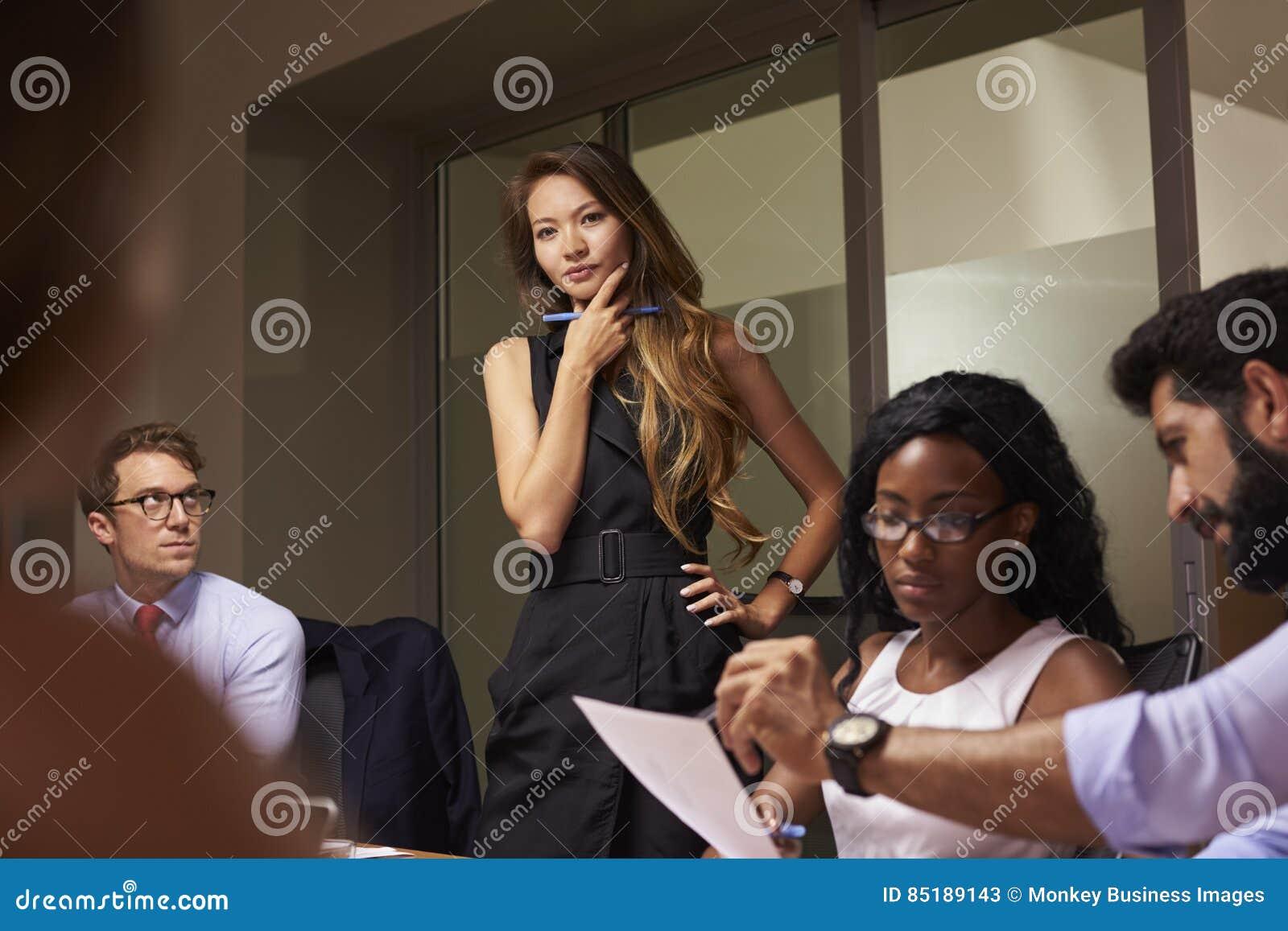 Det kvinnliga framstickandet står tänka på ett aftonaffärsmöte