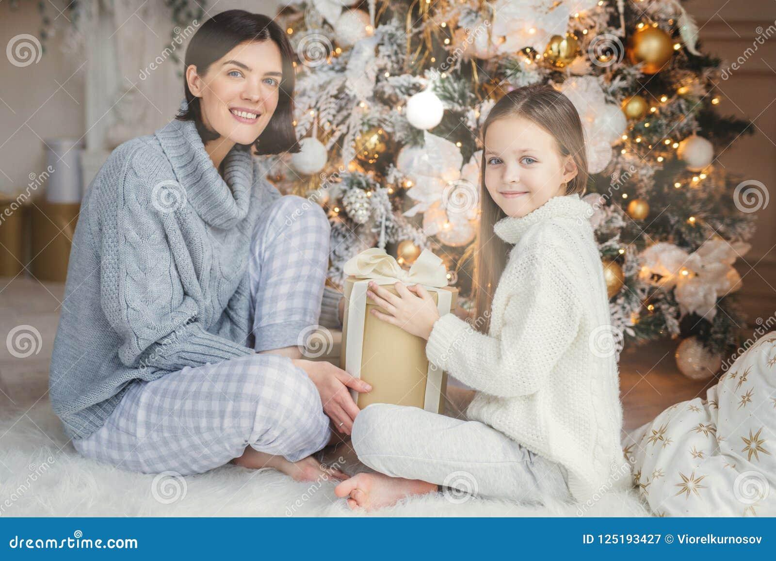 Det lilla barnet och hennes moder sitter på det varma vita trädet för det nya året för matta nära dekorerade, håll framlägger i h