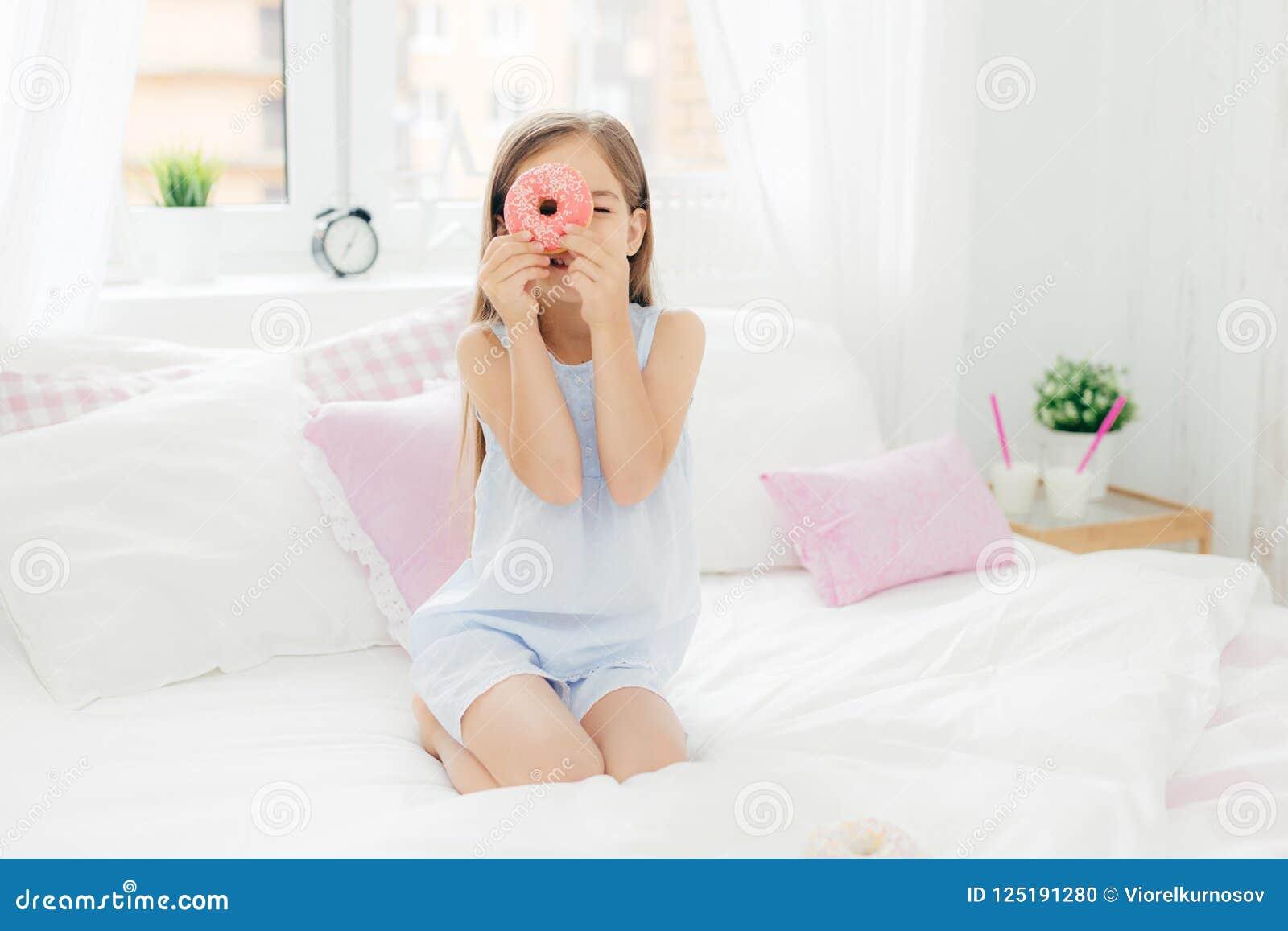 Det lilla nätta kvinnliga barnet rymmer den smakliga söta munken, poserar i sovrum på comfortabled säng, iklädda pyjamas som går