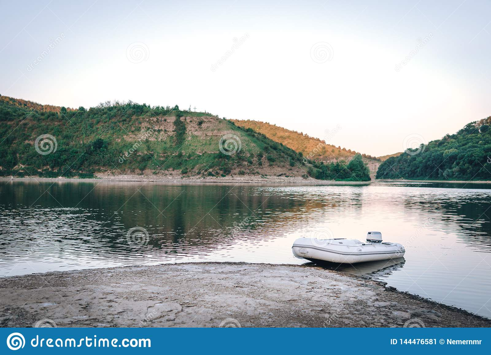 Det lilla vita motorfartyget på bergfloden, solnedgång som fiskar begrepp