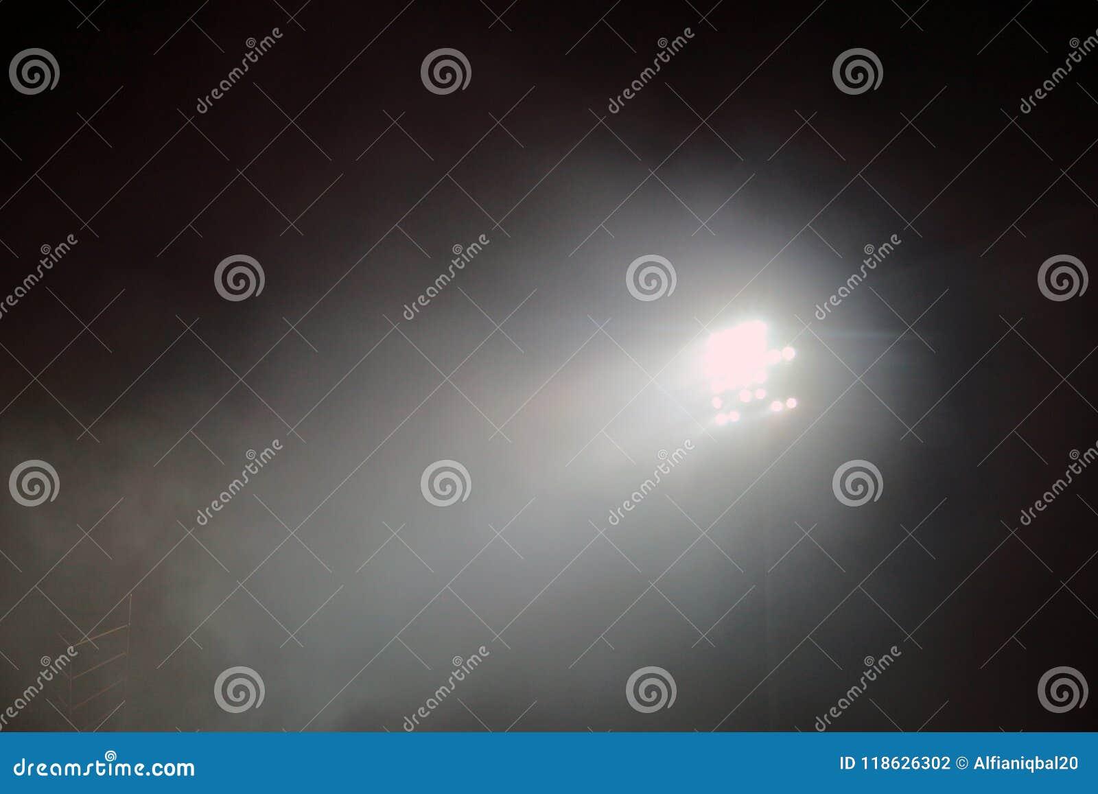 Det ljusa tornet tände på en stadion under nightime Stadionen tänder mot bakgrund för mörkernattsky Stadionljus och rök