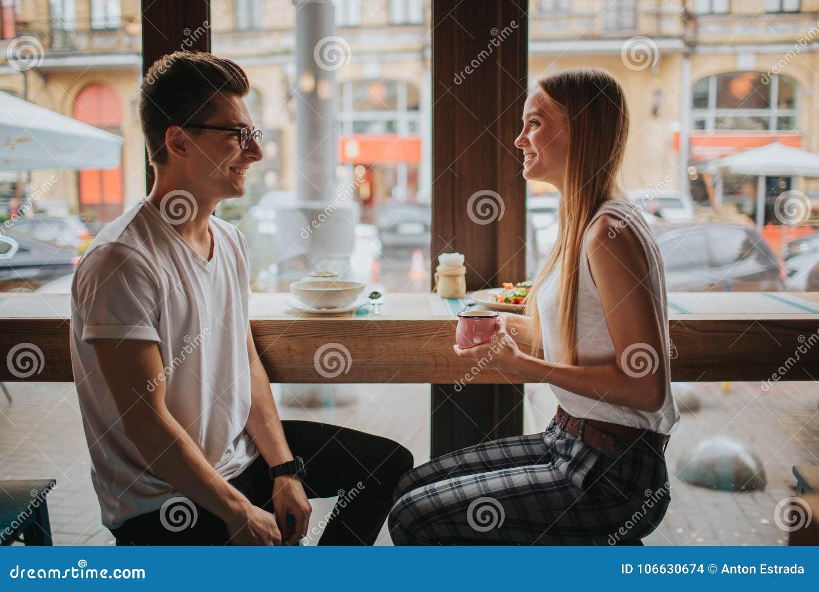 Det lyckliga barnet kopplar ihop förälskat ha ett trevligt datum i en stång eller en restaurang Dem som berättar några berättelse