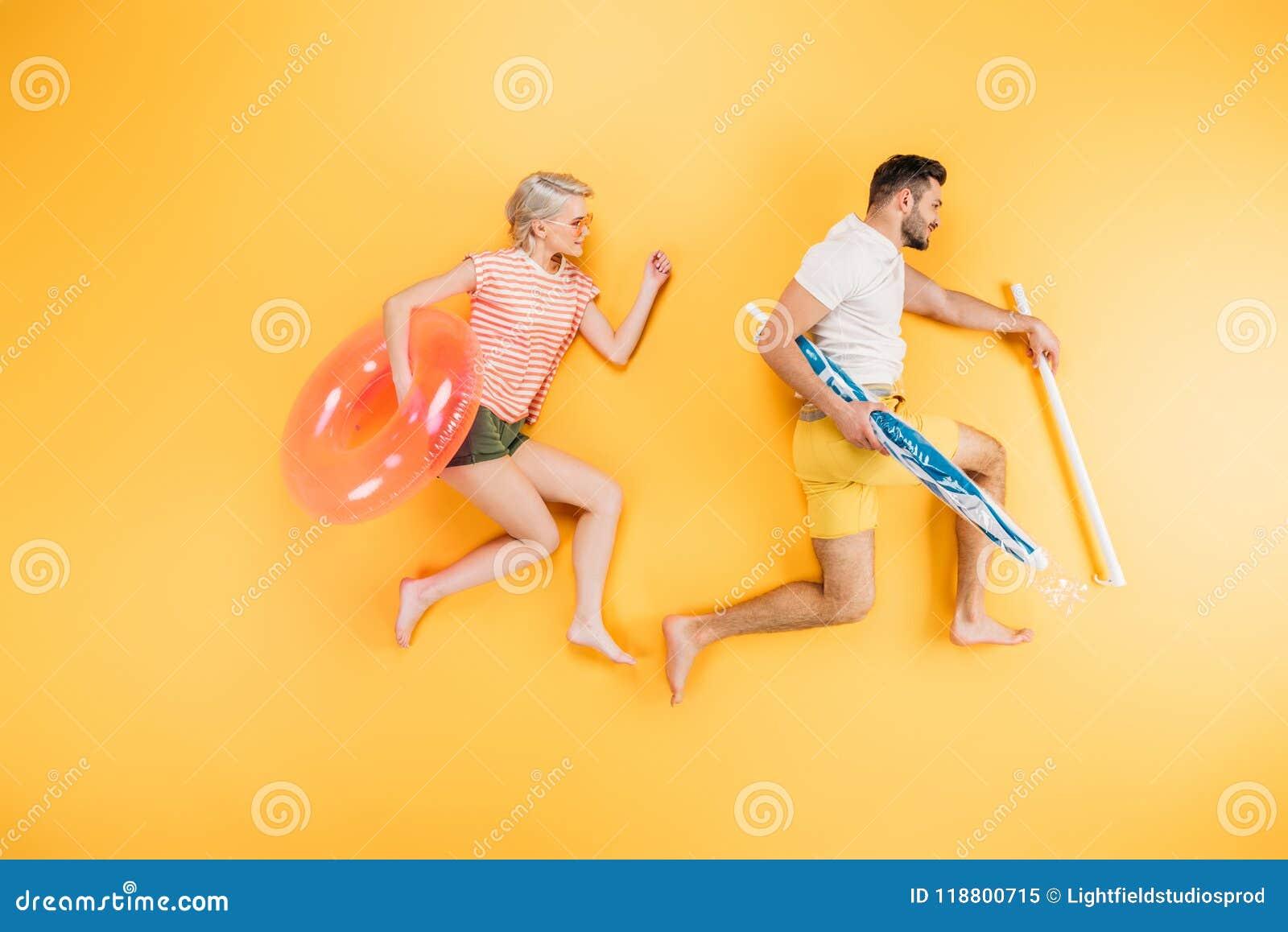 Det lyckliga barnet kopplar ihop det hållande strandparaplyet och simningcirkeln på guling, sommar