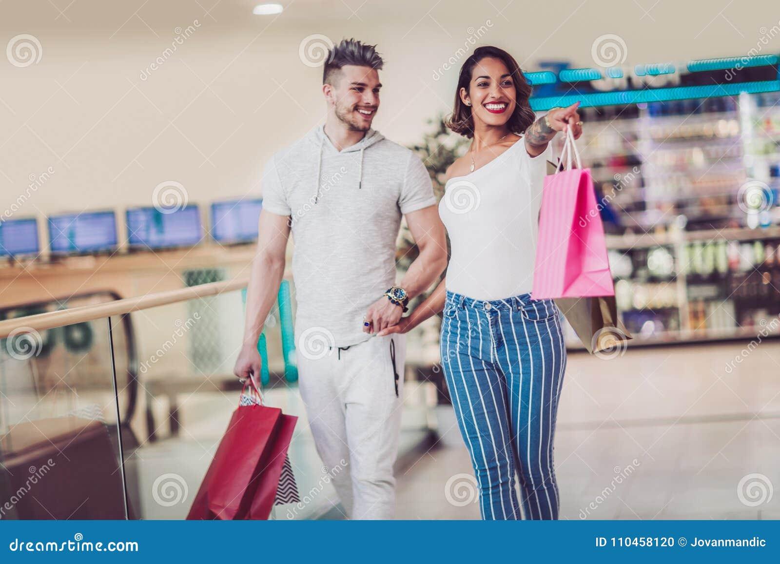 Det lyckliga barnet kopplar ihop med shoppingpåsar som går i galleria