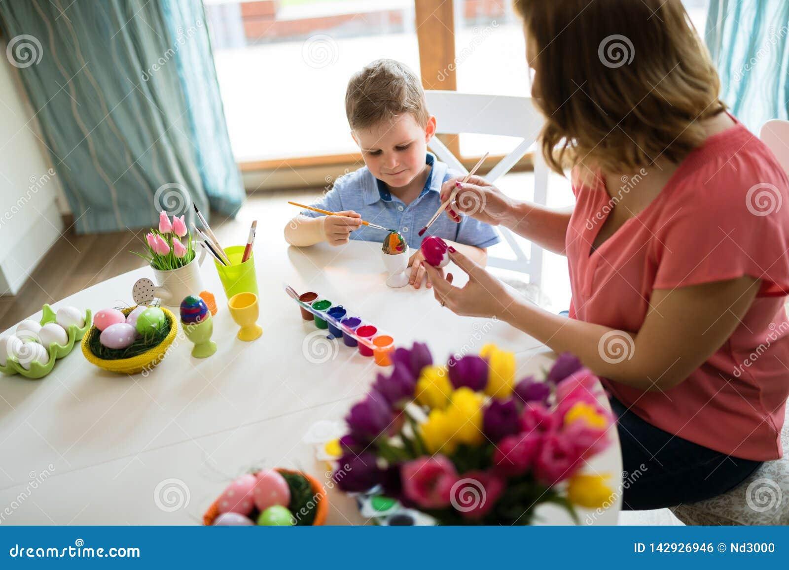 Det lyckliga barnet moder och son målar påskägg
