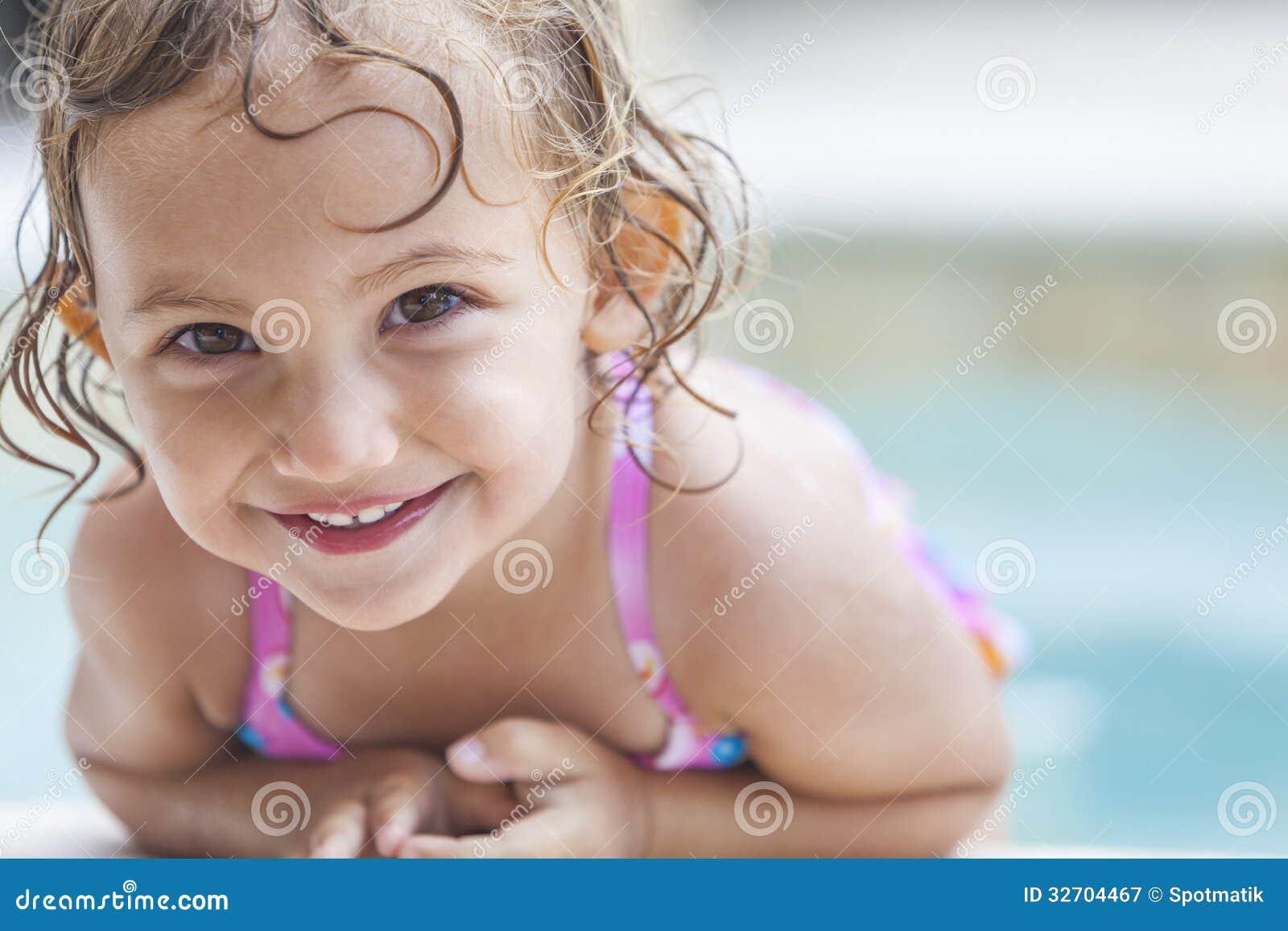 Det lyckliga flickabarnet behandla som ett barn i simbassäng