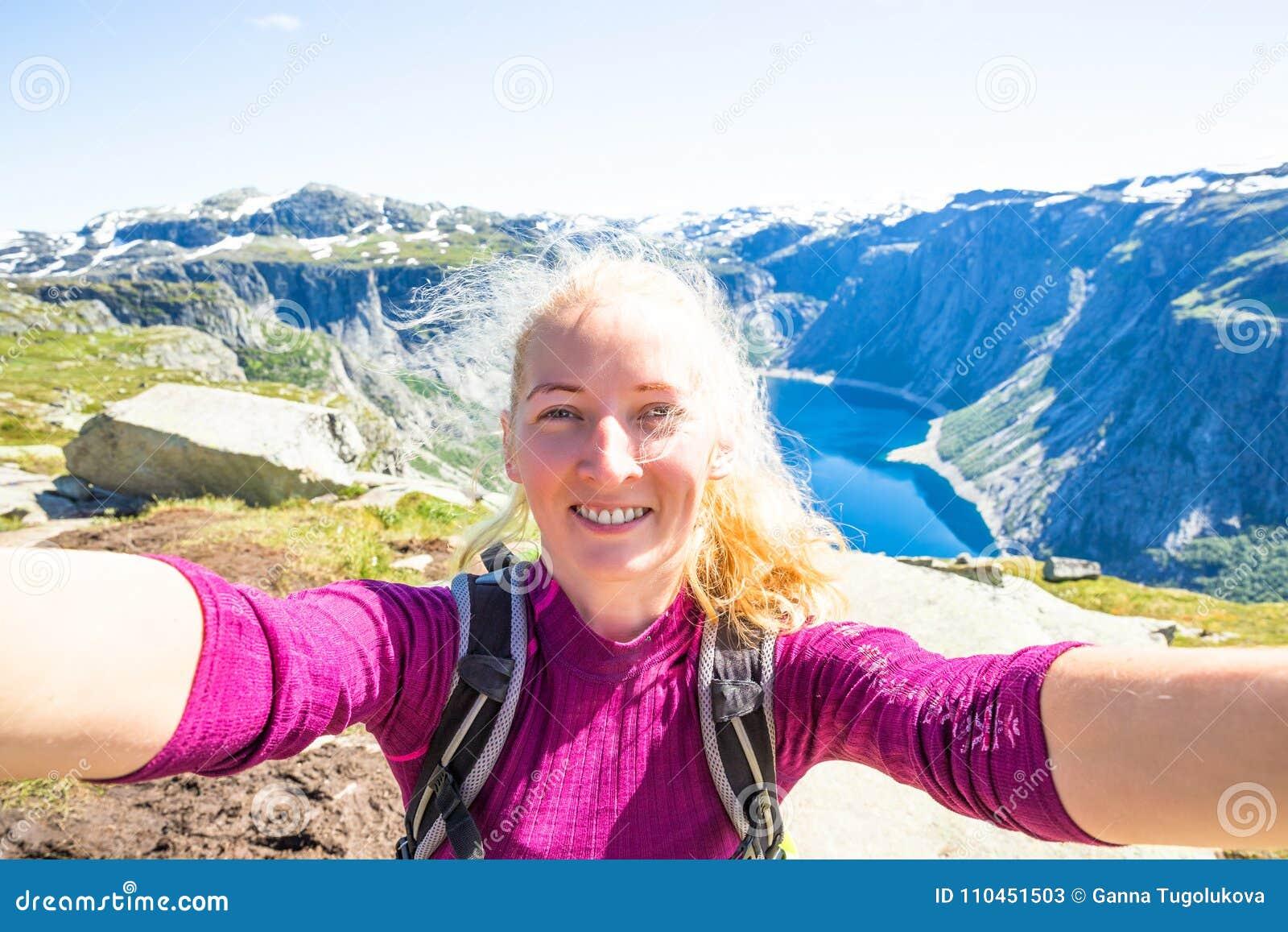 Det lyckliga folket kopplar av i klippa under turen Norge Trolltunga som fotvandrar rutten