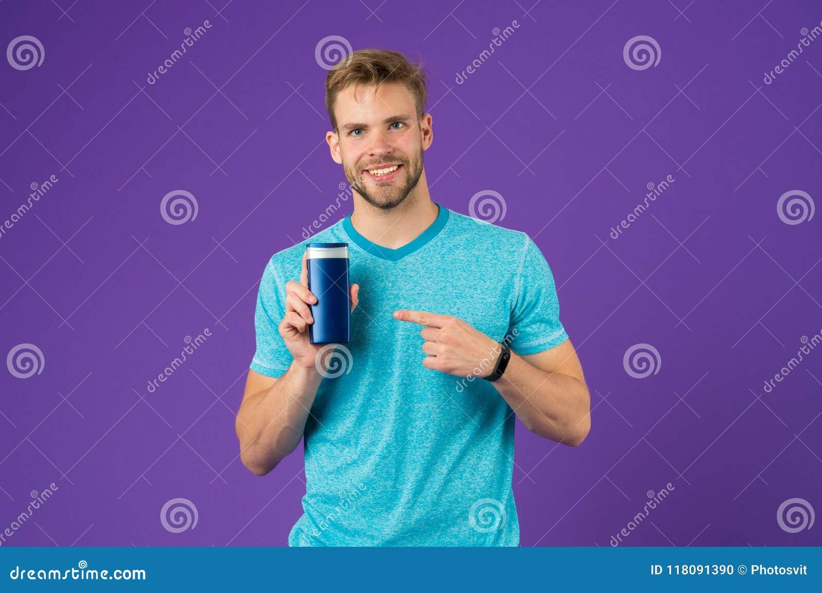 Det lyckliga manpunktfingret på stelnar röret på violett bakgrund Skäggigt manleende med schampoflaskan Skincare och håromsorg
