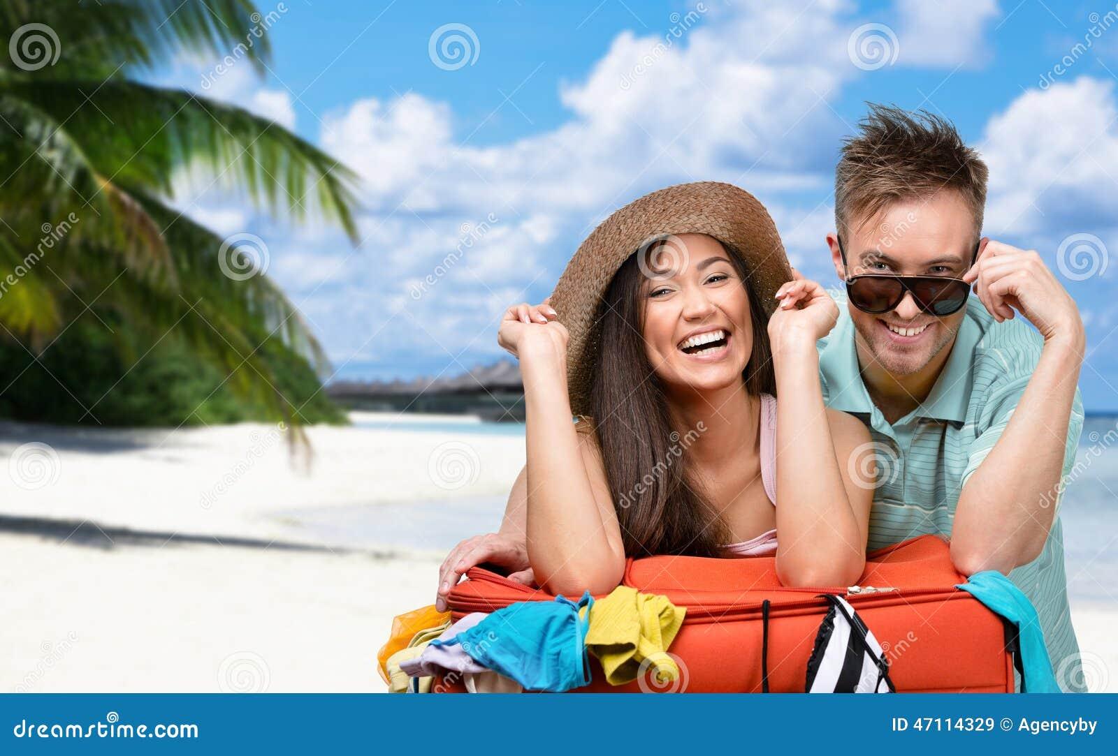 Det lyckliga paret packar upp resväskan med kläder för att resa