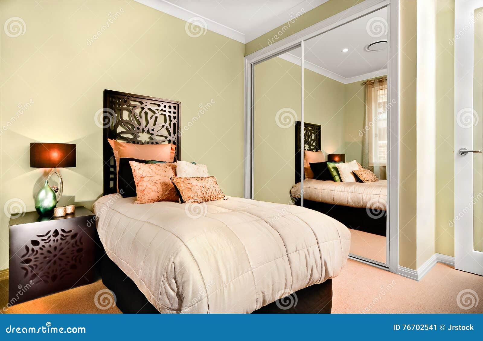 Det lyxiga inre sovrummet på natten med en modern enkel säng inkluderar