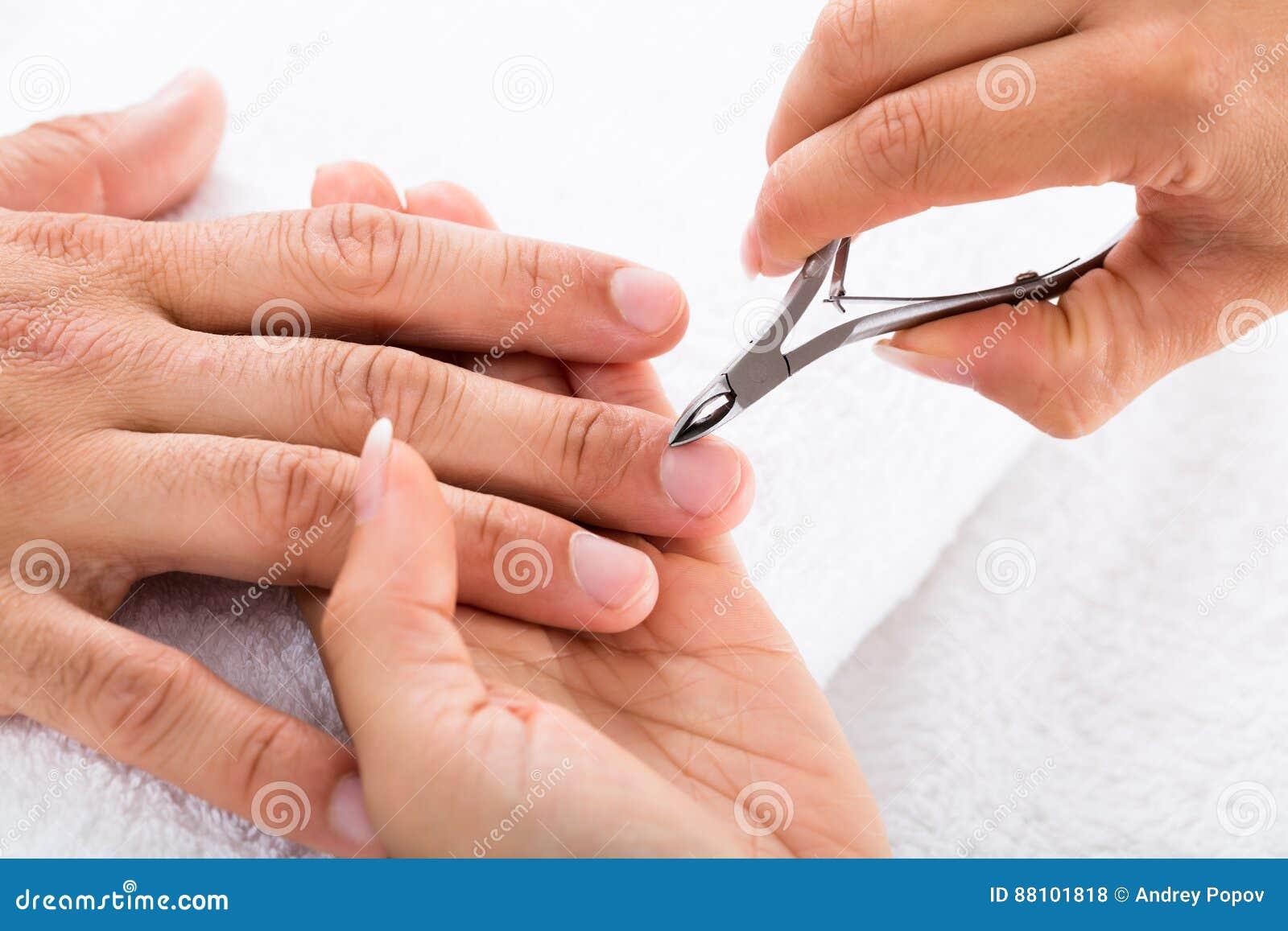 Det manikyristCutting Off The nagelbandet från person`en s fingrar