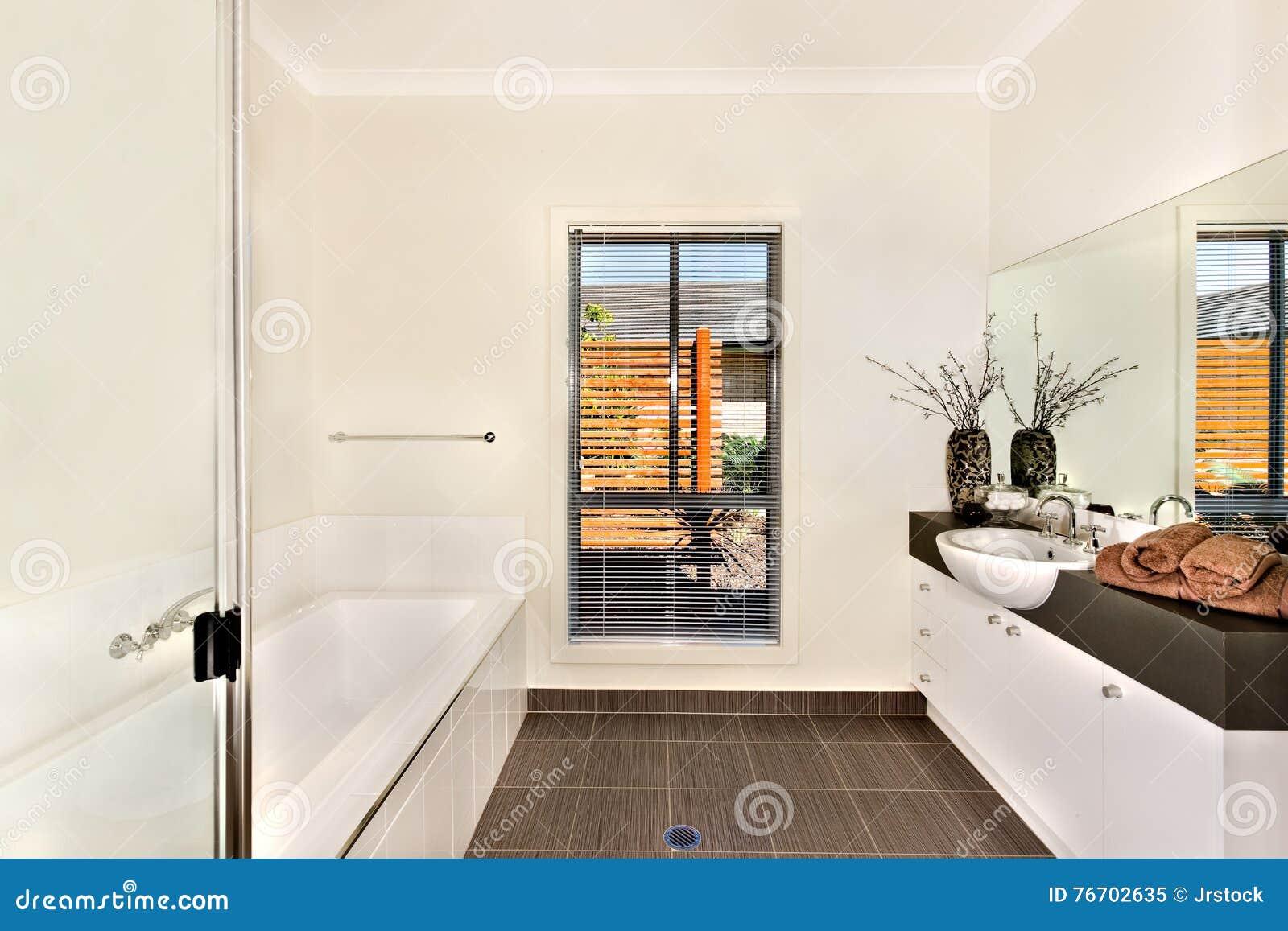 Det moderna badrummet med ett vatten badar och badningområde som är motsatt till th