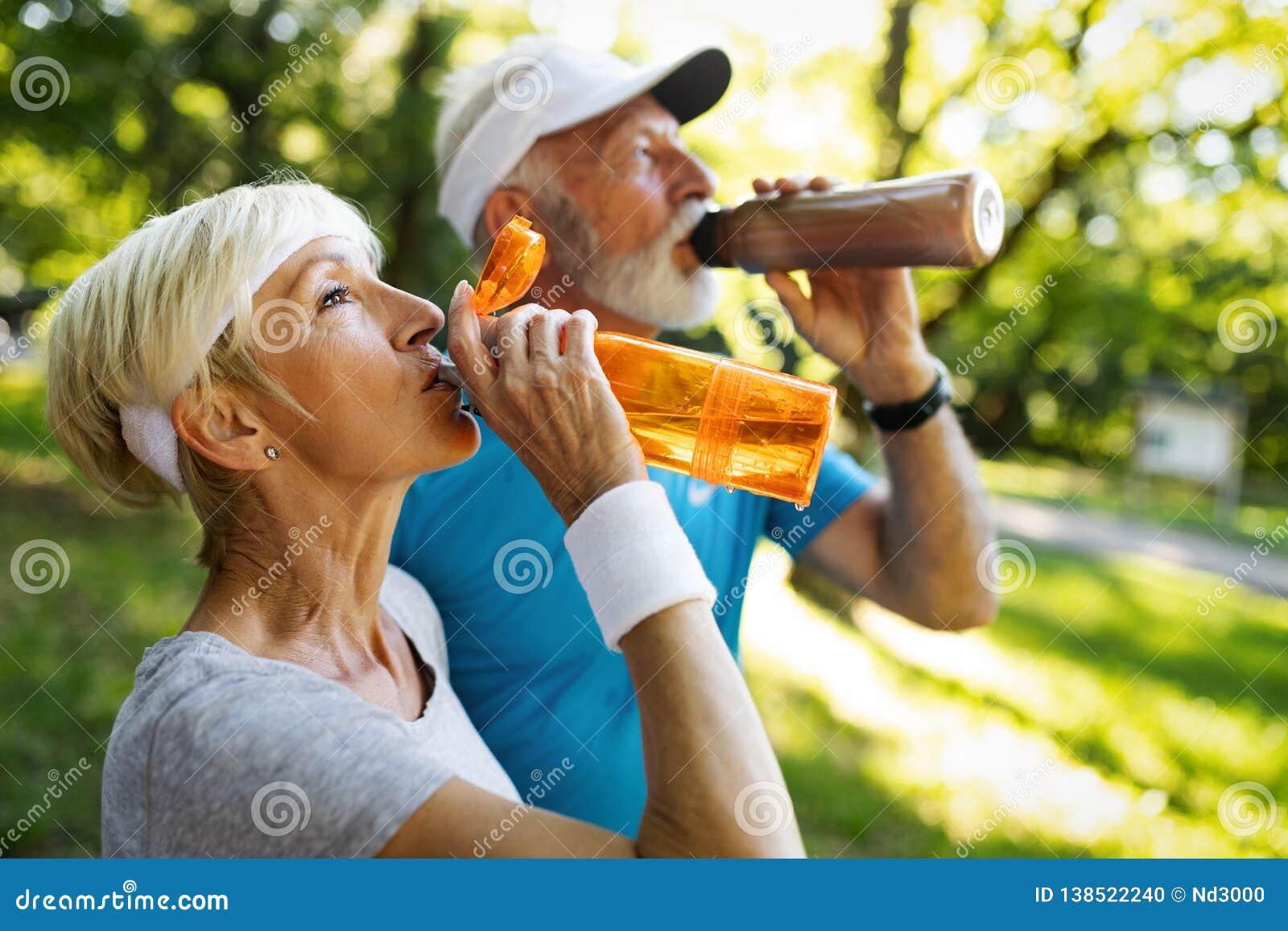 Det mogna paret dricker vatten för att fylla på energi och för att hydratisera