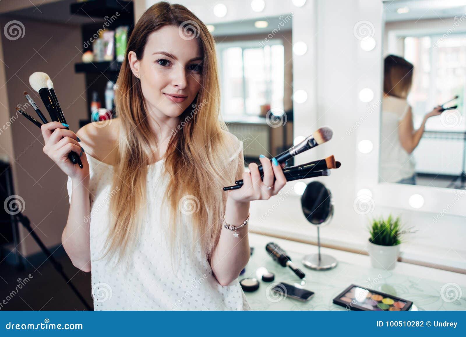 Det nätta le kvinnaanseendet med en variation av sminket borstar på skönhetstudion