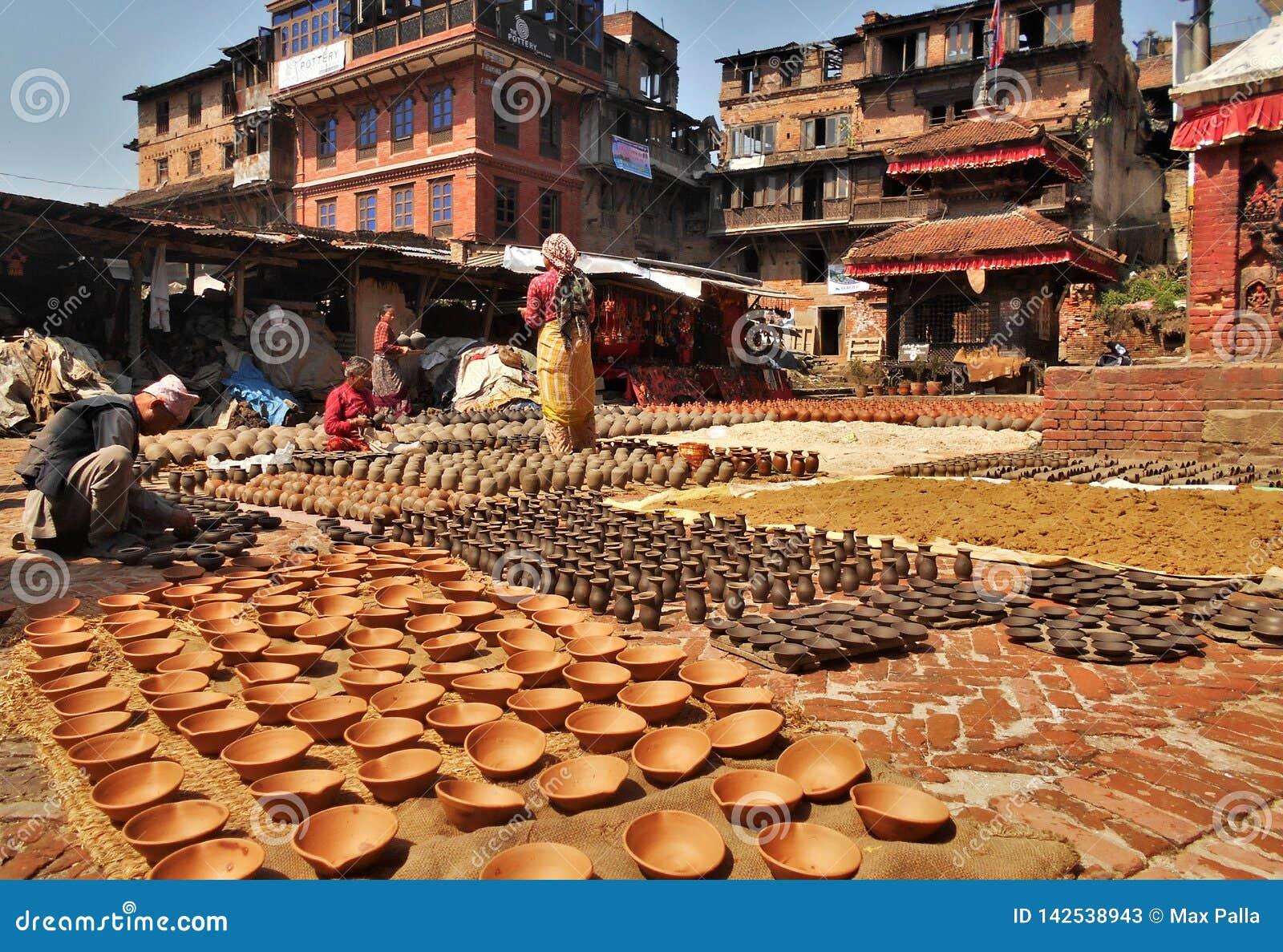 Det nepalesiska folket är forma och torka upp keramikkrukor i krukmakerifyrkant