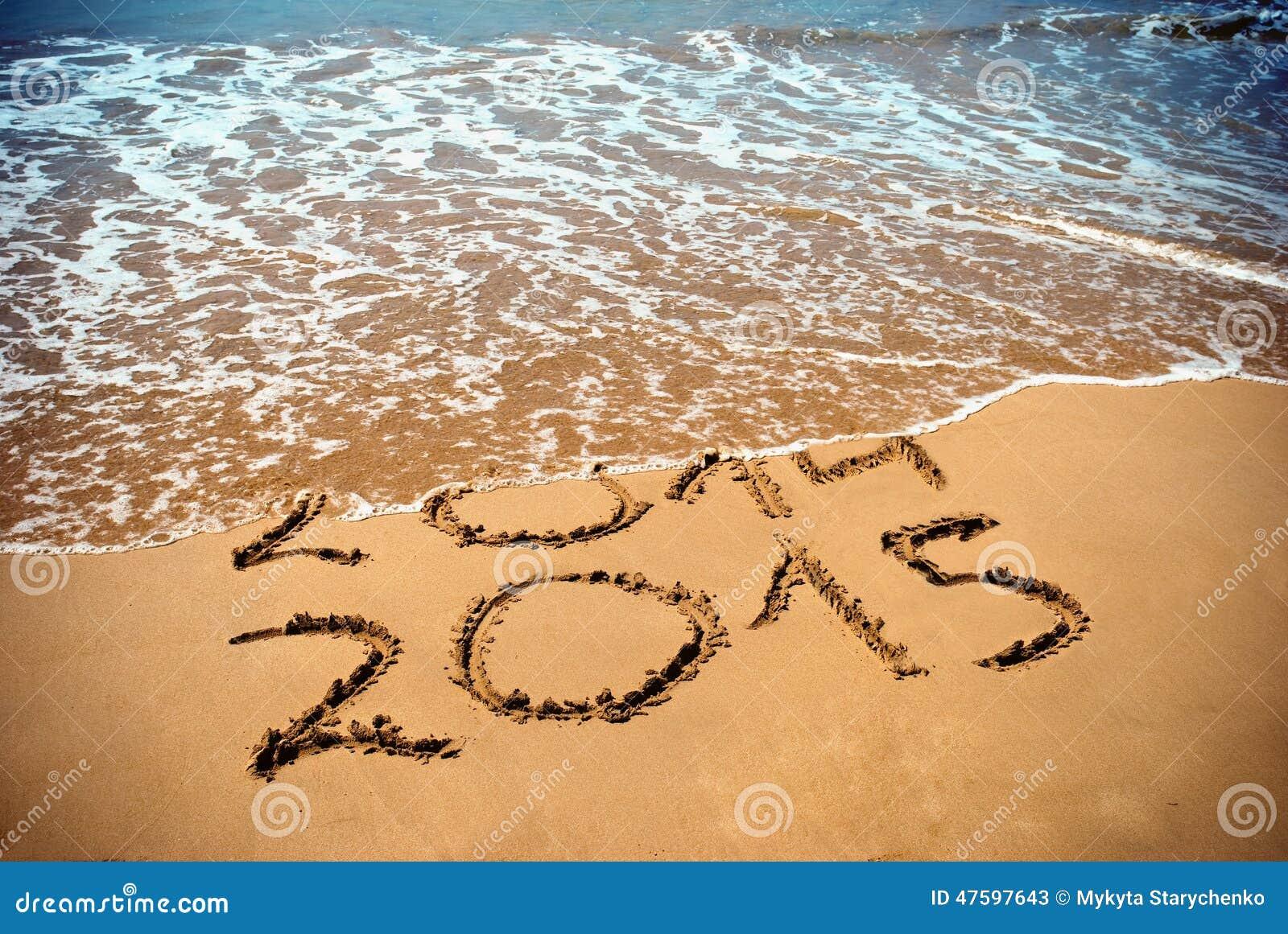 Det nya året 2015 är det kommande begreppet - inskriften 2014 och 2015 på en strandsand