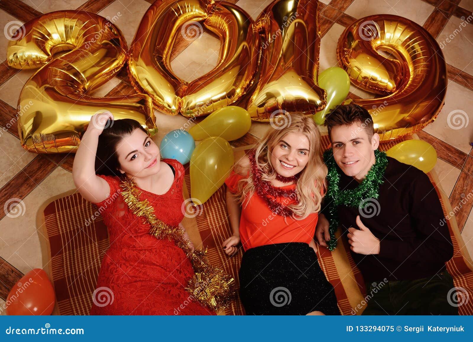Det nya 2019 året är kommande Grupp av gladlynta ungdomarsom bär guld- kulöra nummer och att ha gyckel på partiet