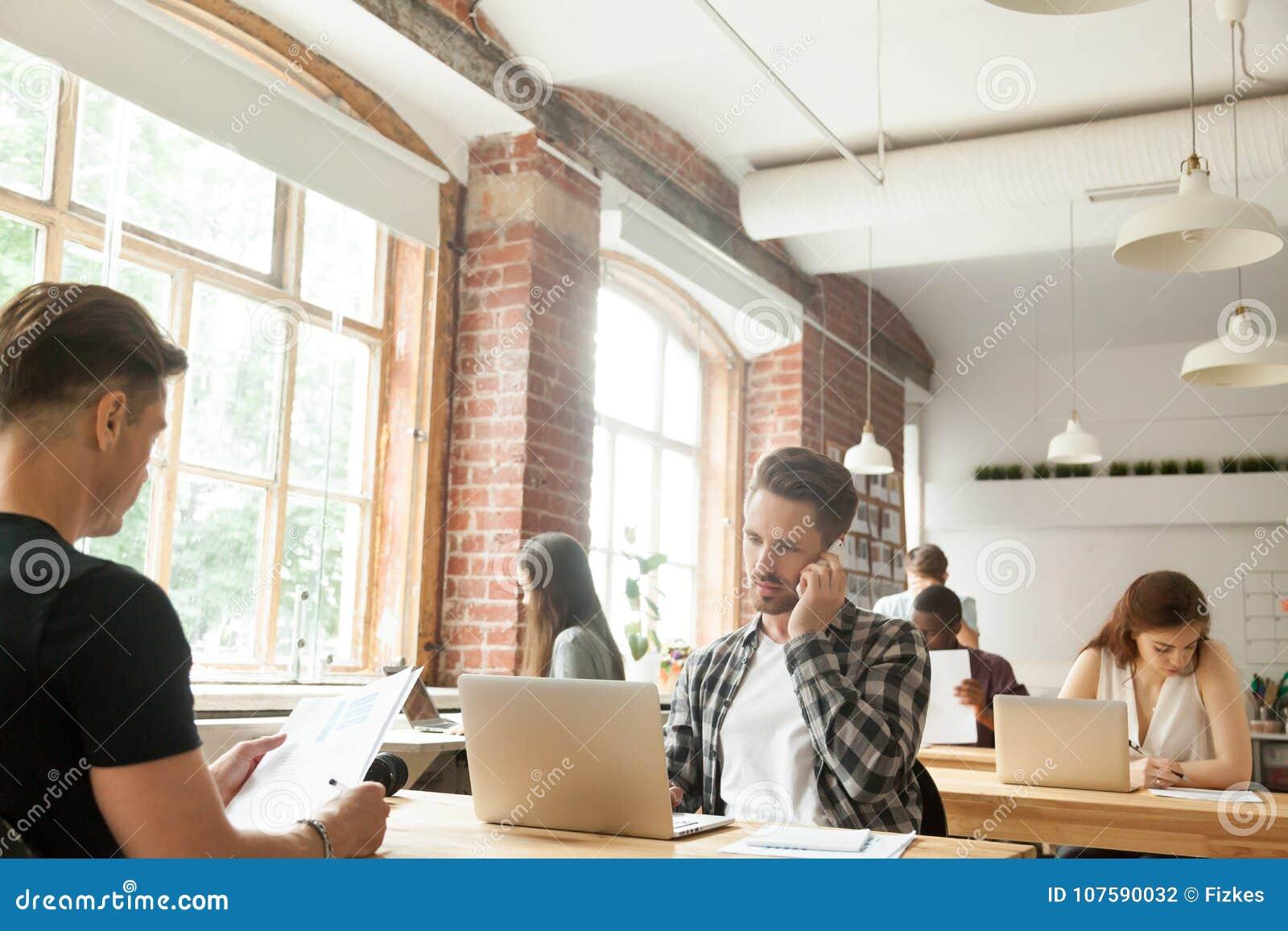 Det olika folket fokuserade på arbete i modernt vindCo-arbete utrymme