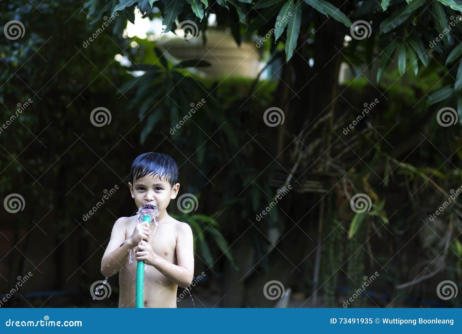 Det pojkar spelade vattnet i trädgården