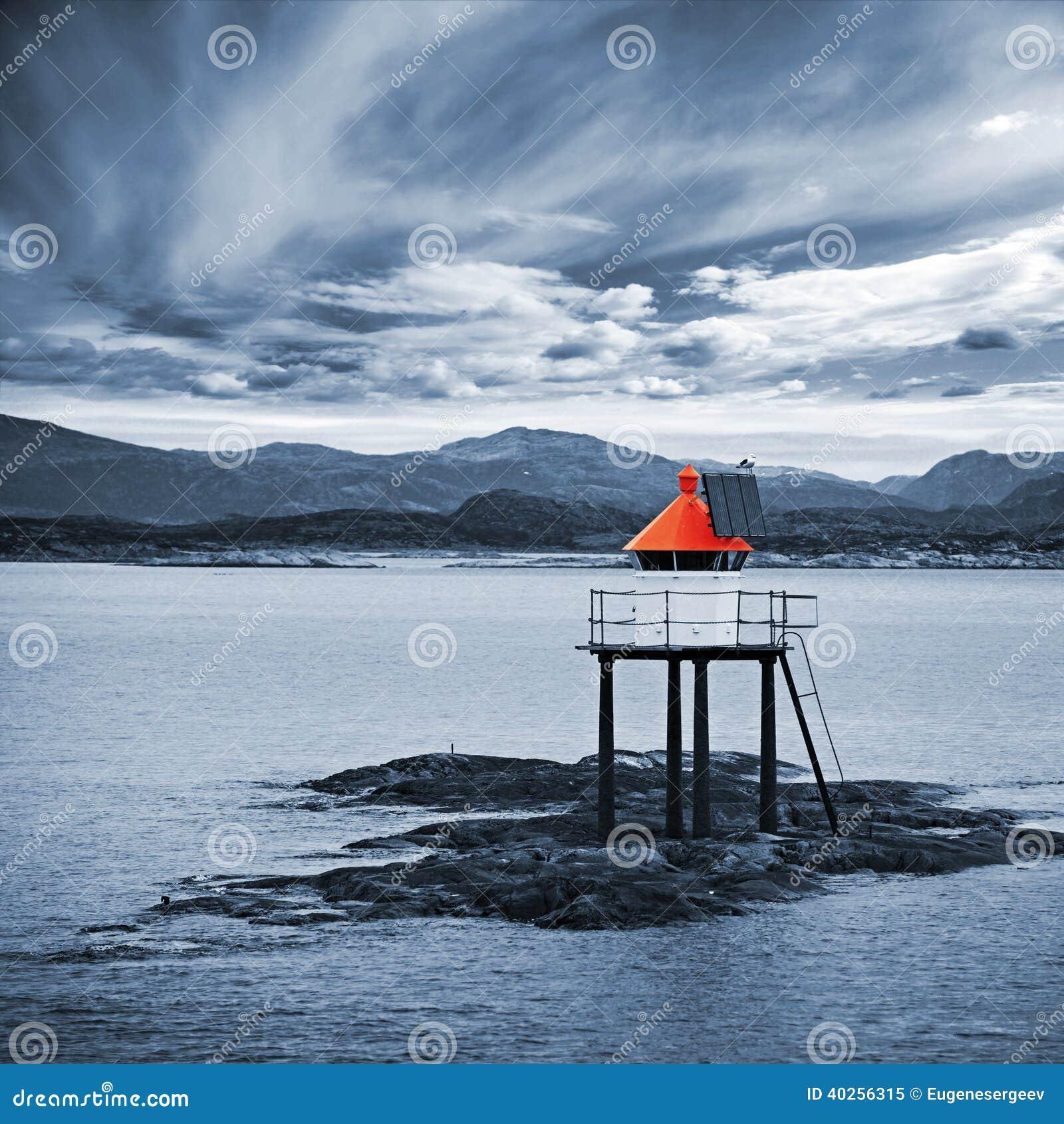 Det röda norska fyrtornet på havet vaggar