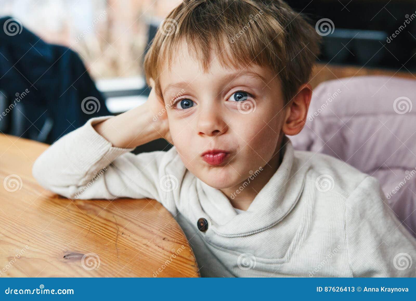 Det roliga Caucasian pyslilla barnet i den vita skjortan som ler danande, vänder mot