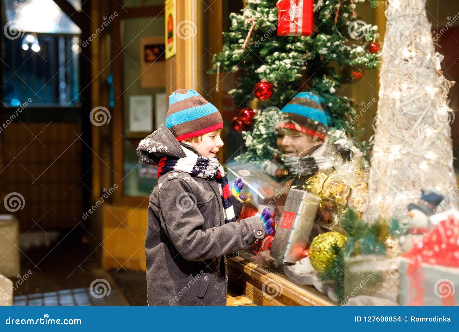 Det roliga lyckliga barnet i modevinter beklär danandefönstershopping som dekoreras med gåvor, xmas-träd